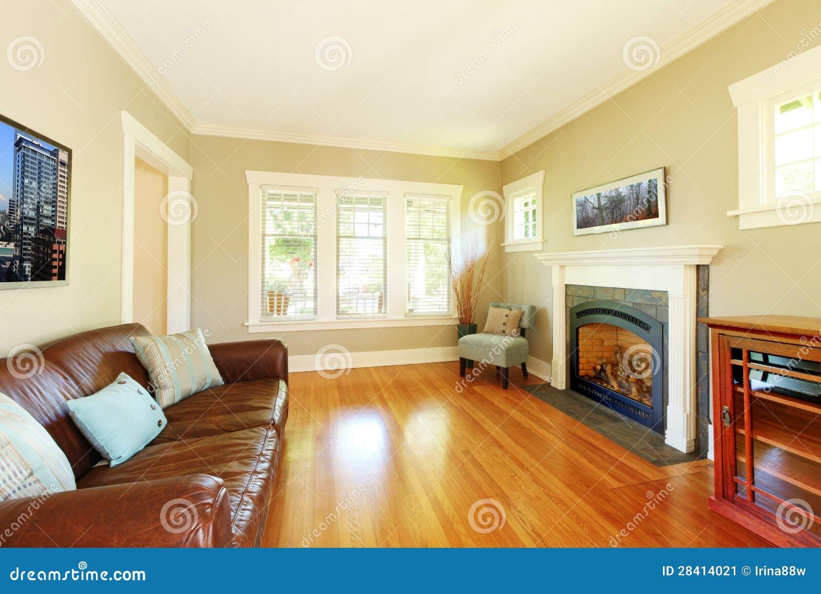Elegante woonkamer met open haard en leerbank met beige muren ...