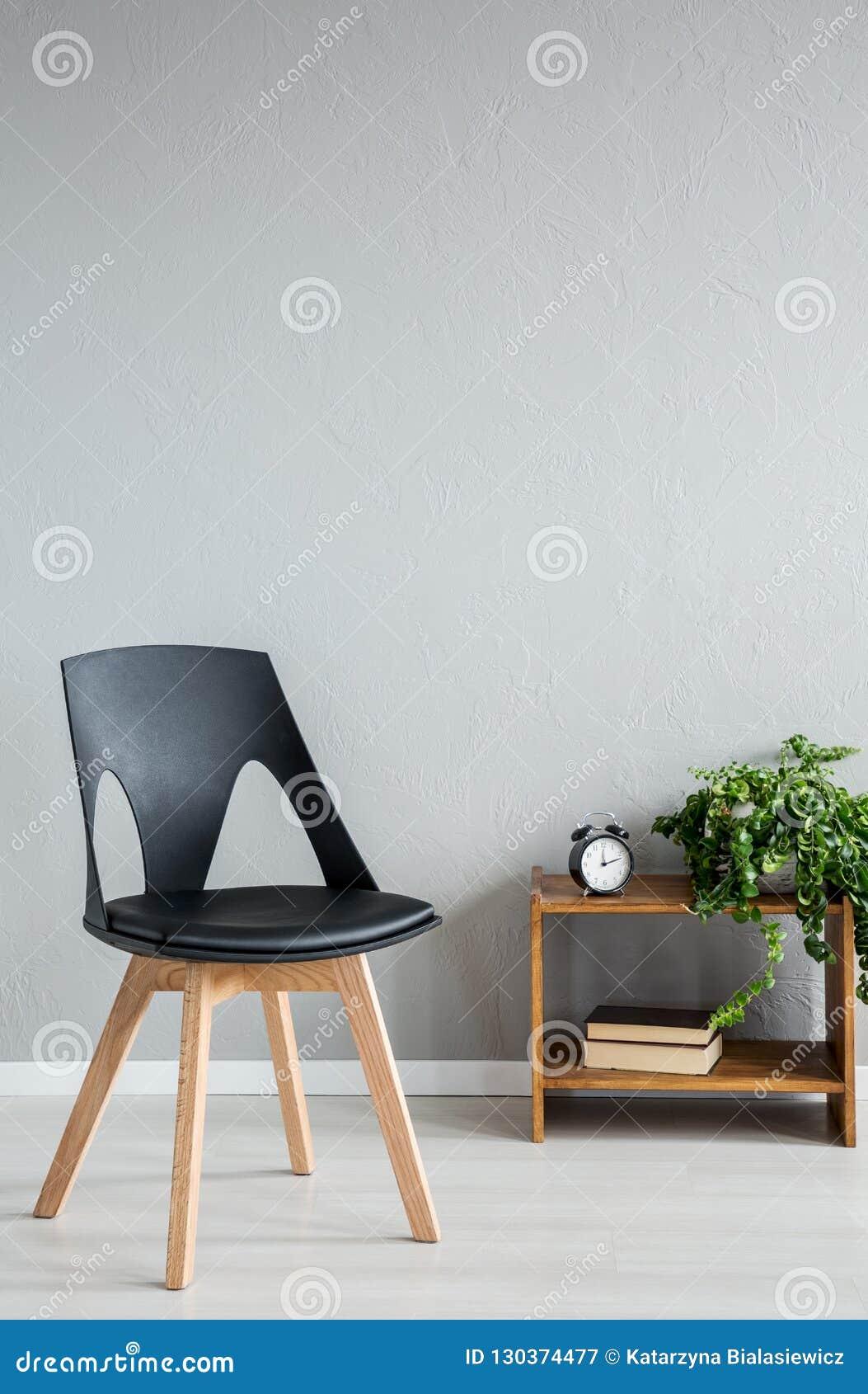 Elegante zwarte houten stoel naast kabinet met klok en bloemen in modern bureaubinnenland