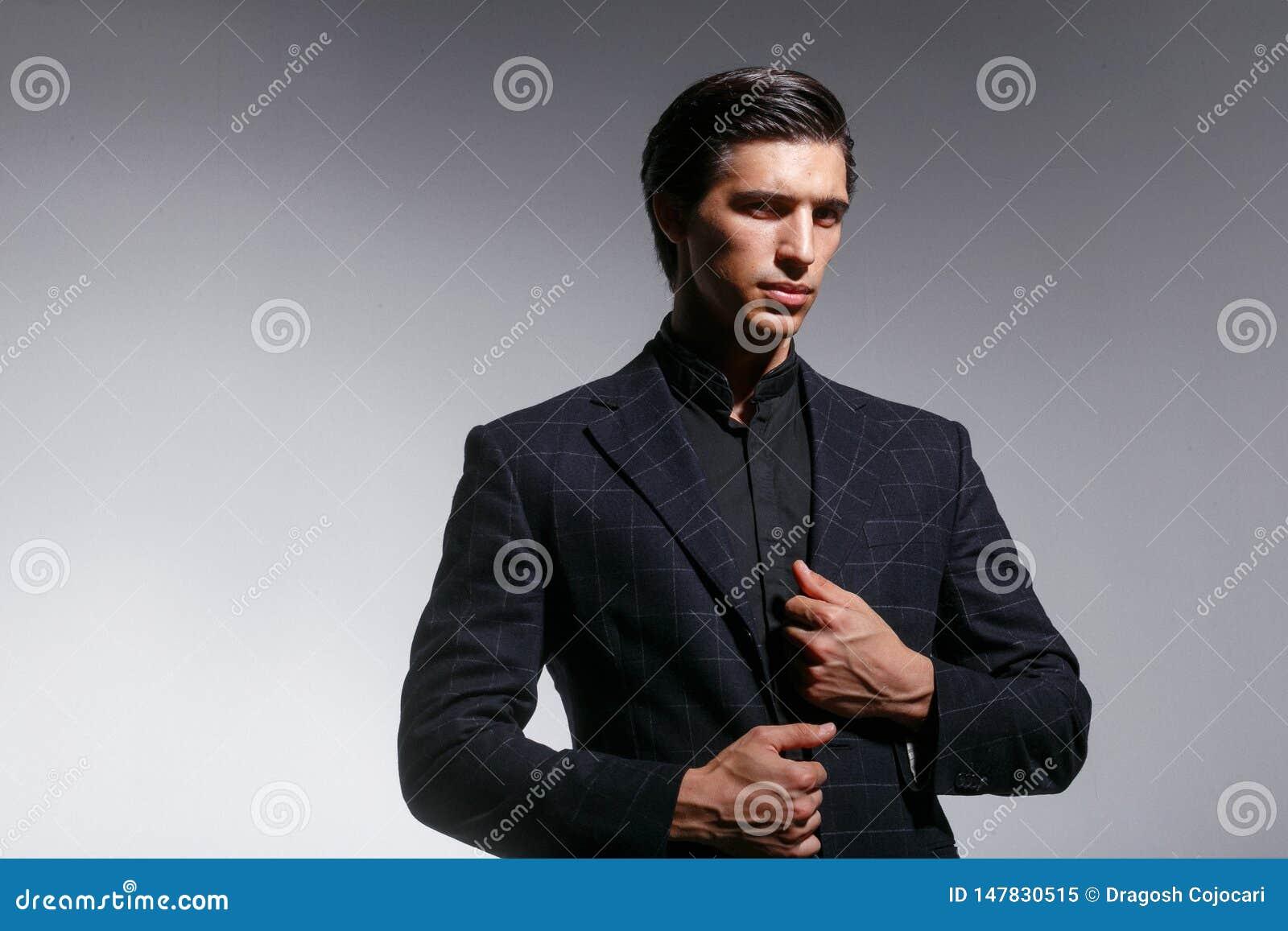 Eleganter junger Mann in der Klage, vereinbart seine Klage, Haute Couture-Konzept, auf einem weißen Hintergrund Horizontale Ansic