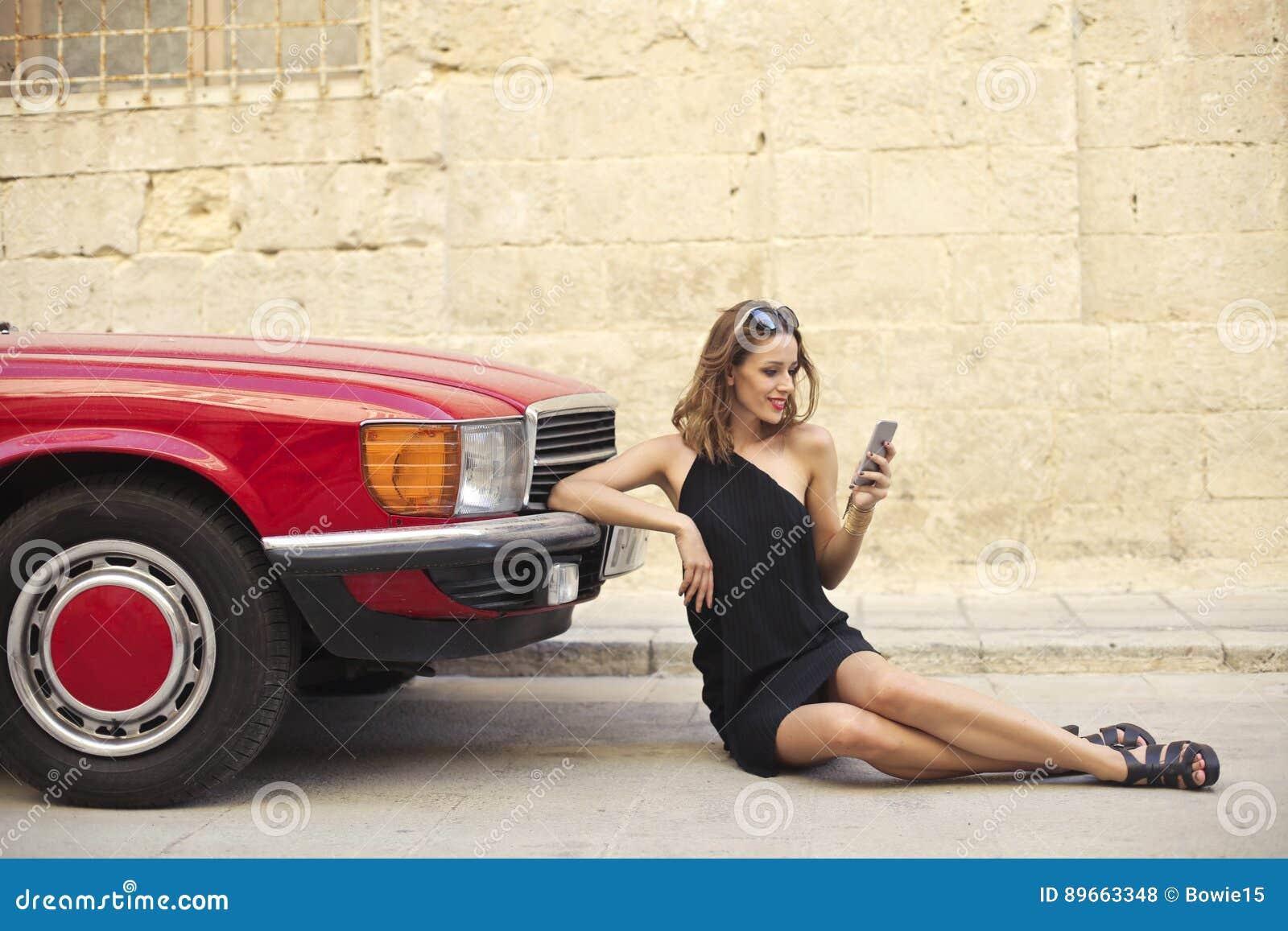 Elegantes Mädchen, das einen Smartphone nahe bei einem Auto verwendet