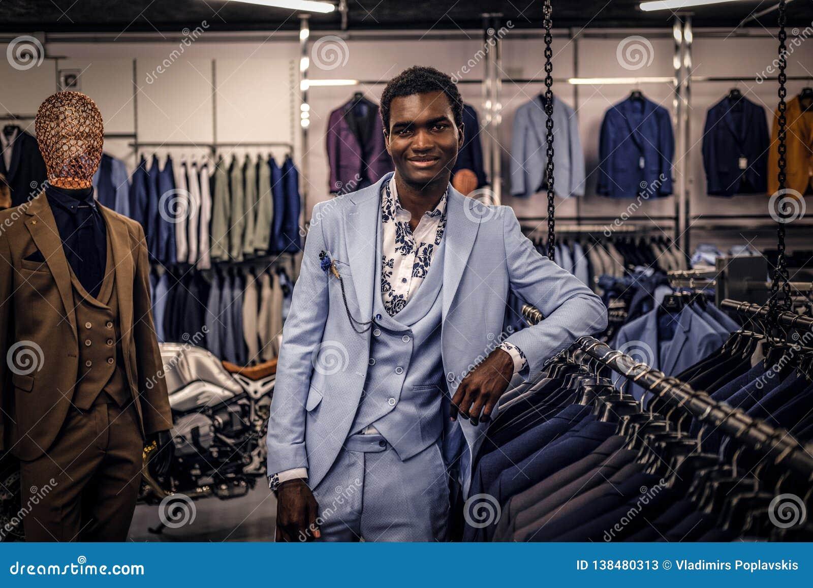 Elegantly klädd afrikansk amerikanman som lutar på en skyltdocka i ett klassiskt menswearlager