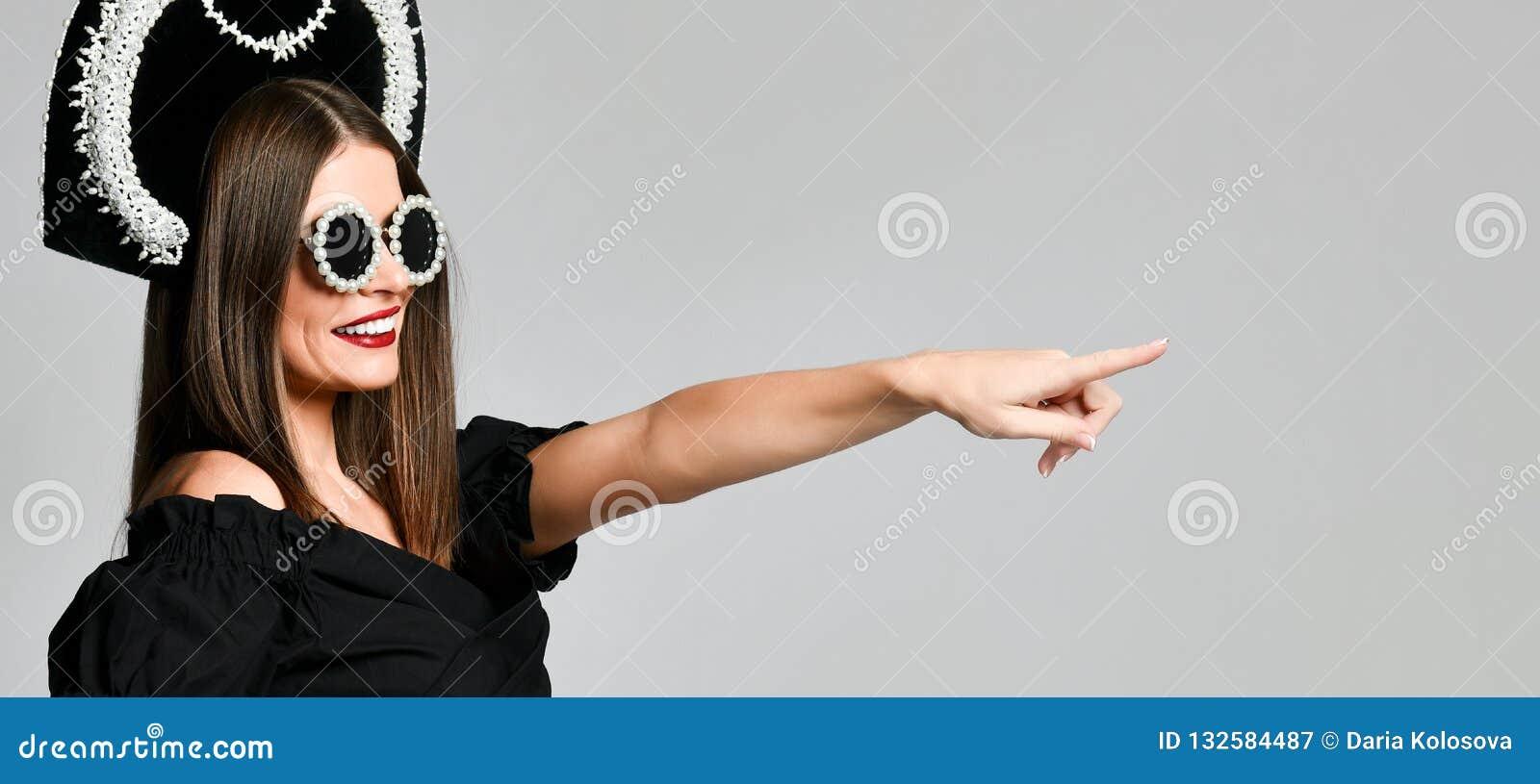 Eleganza e stile Ritratto dello studio della giovane donna splendida in poco vestito nero che posa contro il fondo giallo