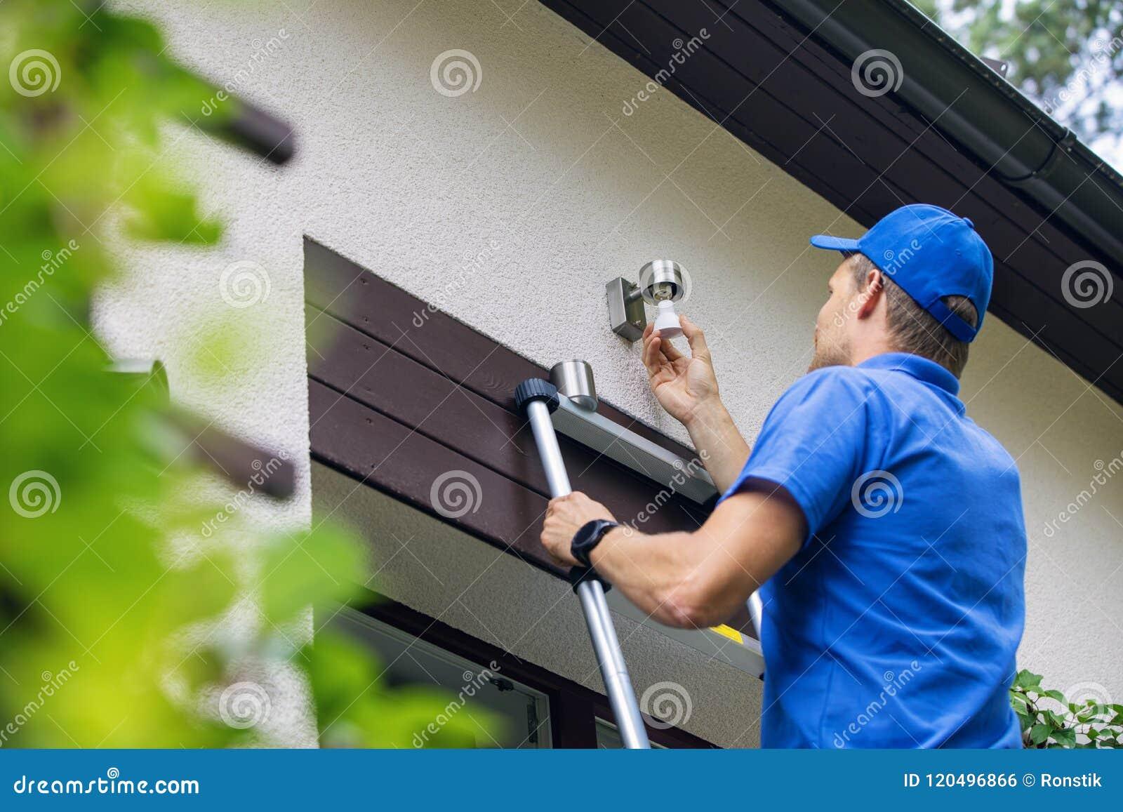 Elektricien de status op ladder en verandert de gloeilamp