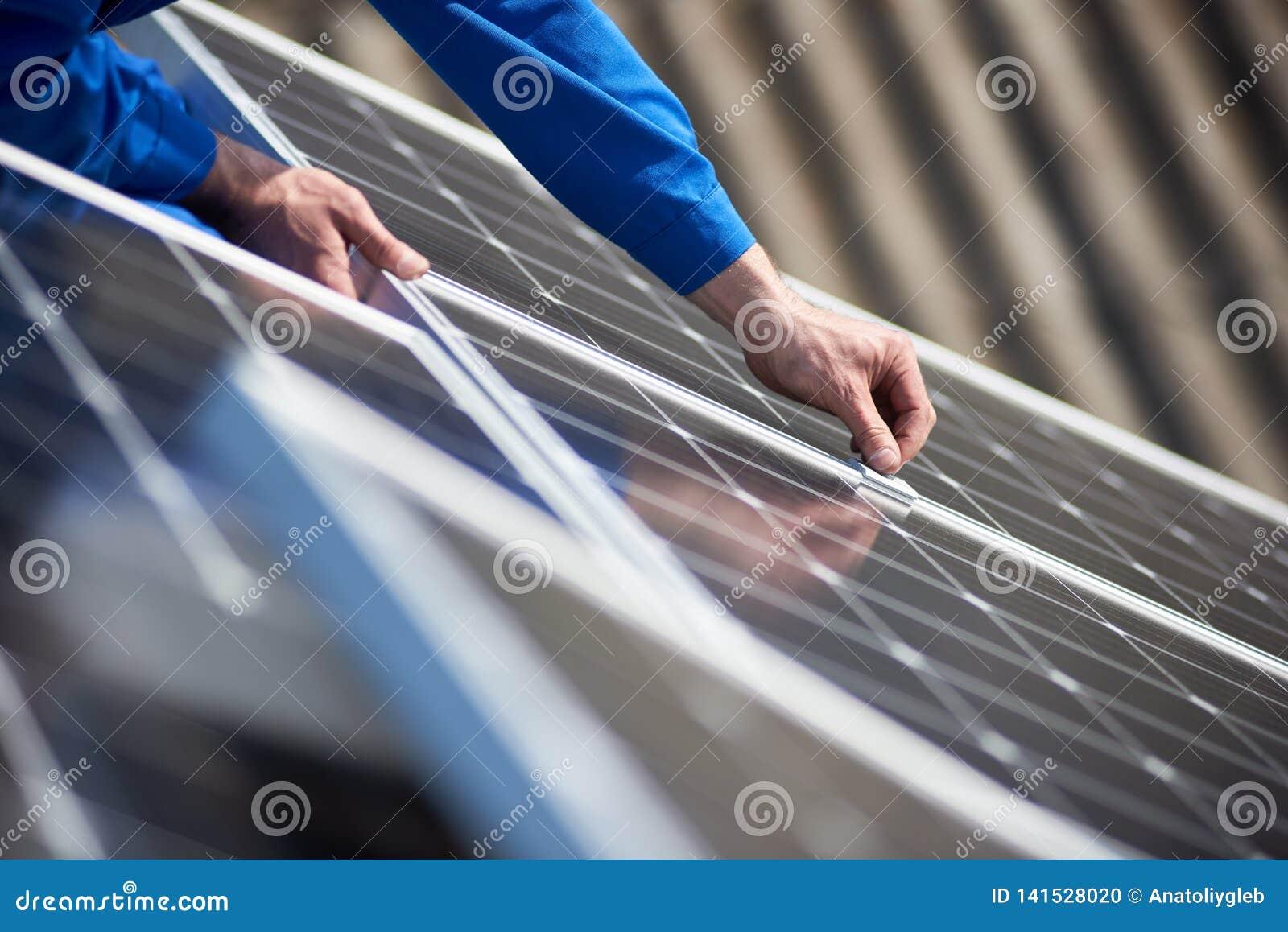 Elektricien opzettend zonnepaneel op dak van modern huis