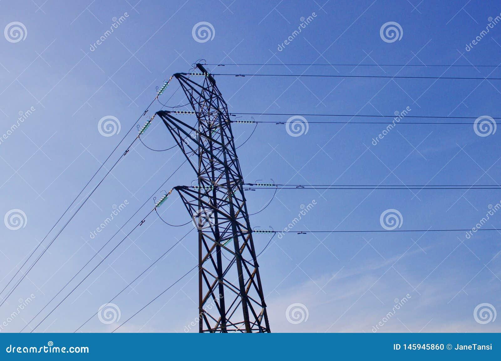 Elektriciteitspyloon met machtskabels tegen blauwe hemelachtergrond