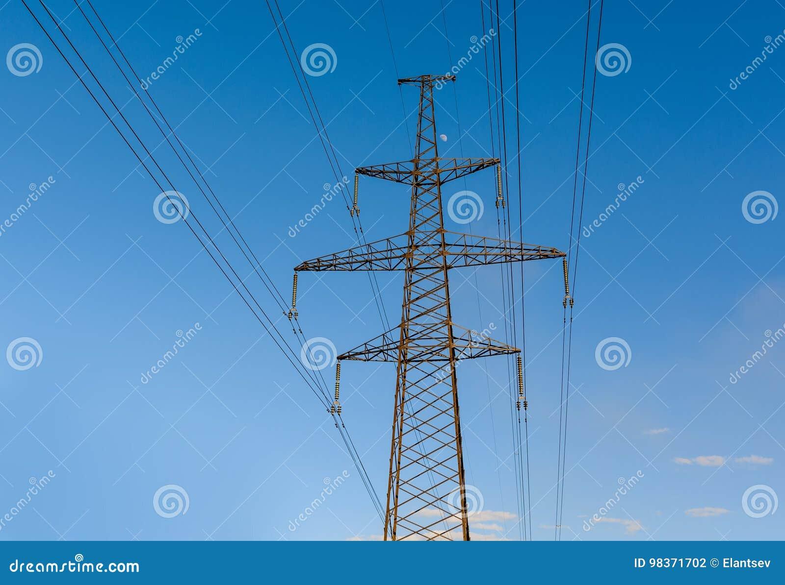 Elektriciteitspyloon tegen blauwe hemelachtergrond die wordt gesilhouetteerd De toren van de hoogspanning
