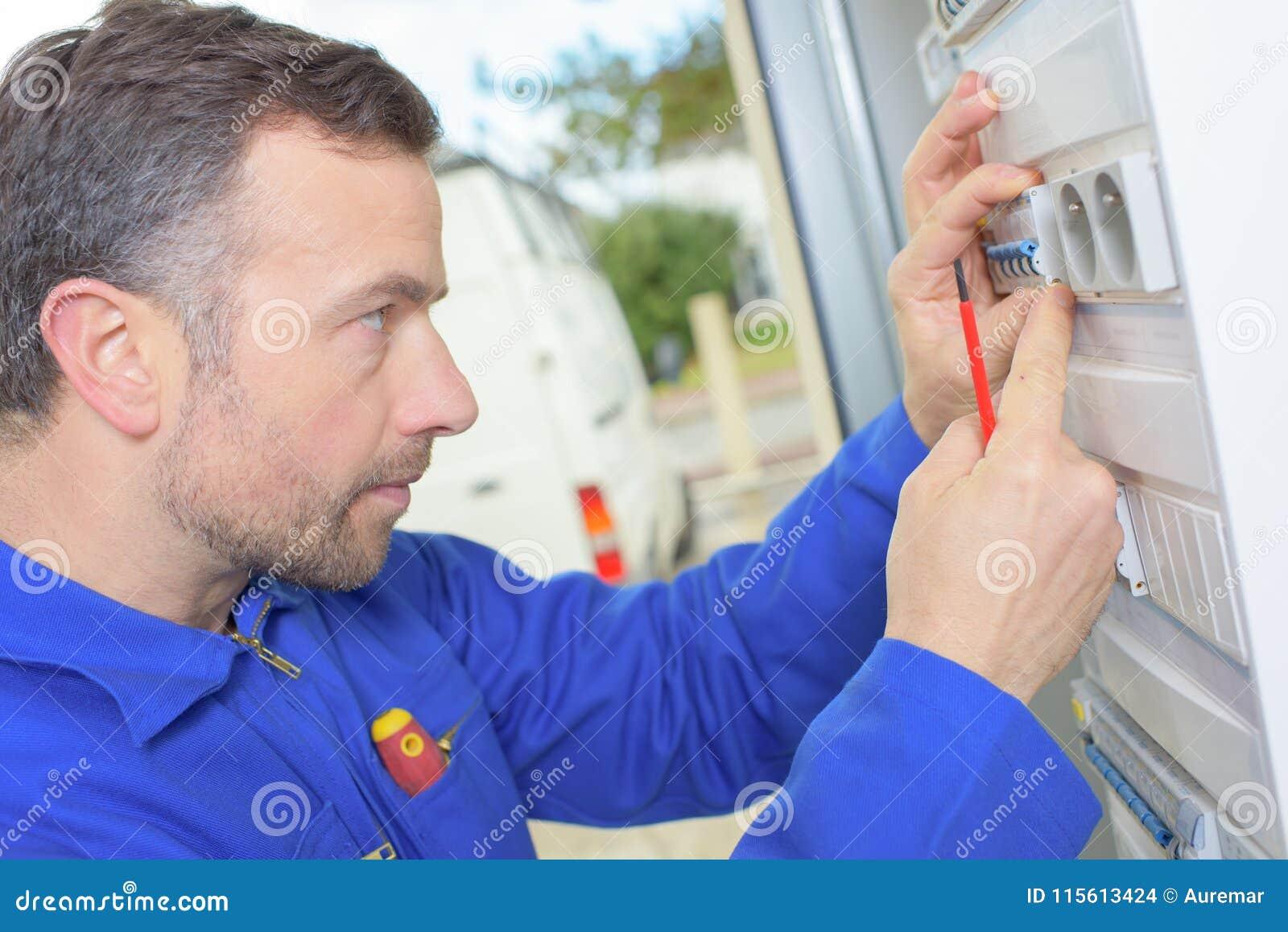 Elektriker, der ein fusebox kontrolliert