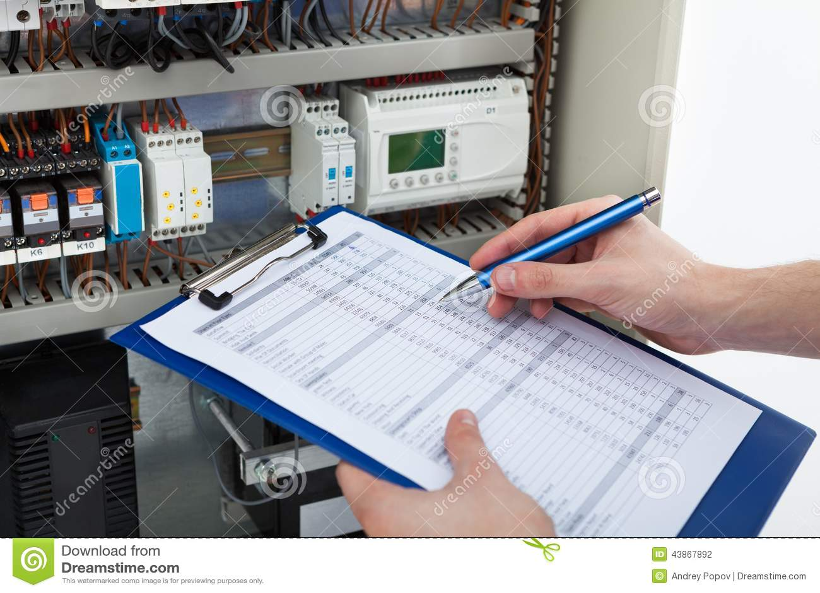 Elektriker, der Klemmbrett bei der Untersuchung von fusebox hält