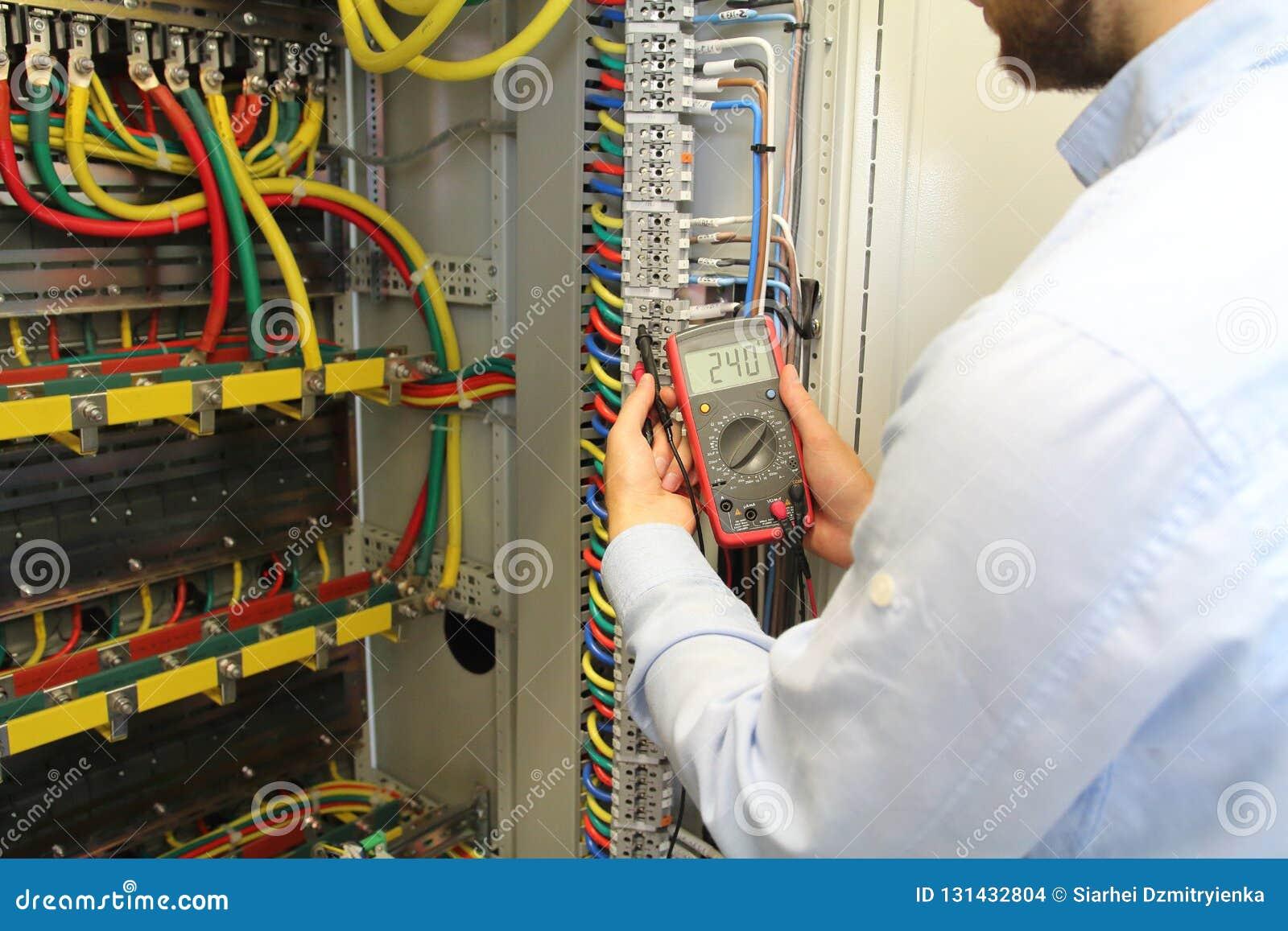 Elektrikeren arbetar i ask för säkring för fördelning för elektriska kablar med multimeteren