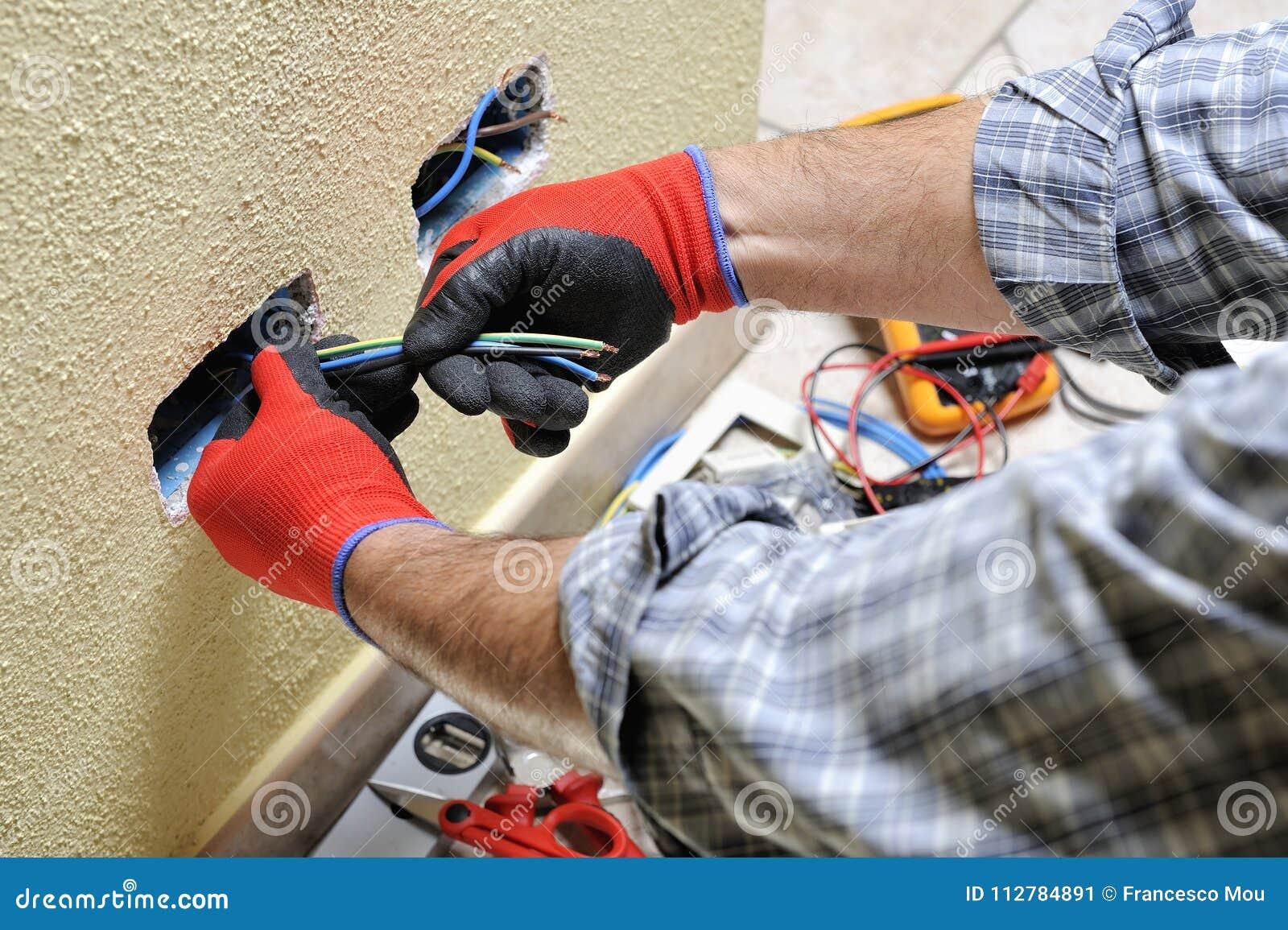 Elektrikertechniker bei der Arbeit mit Schutzausrüstung auf einem elektrischen Wohnsystem
