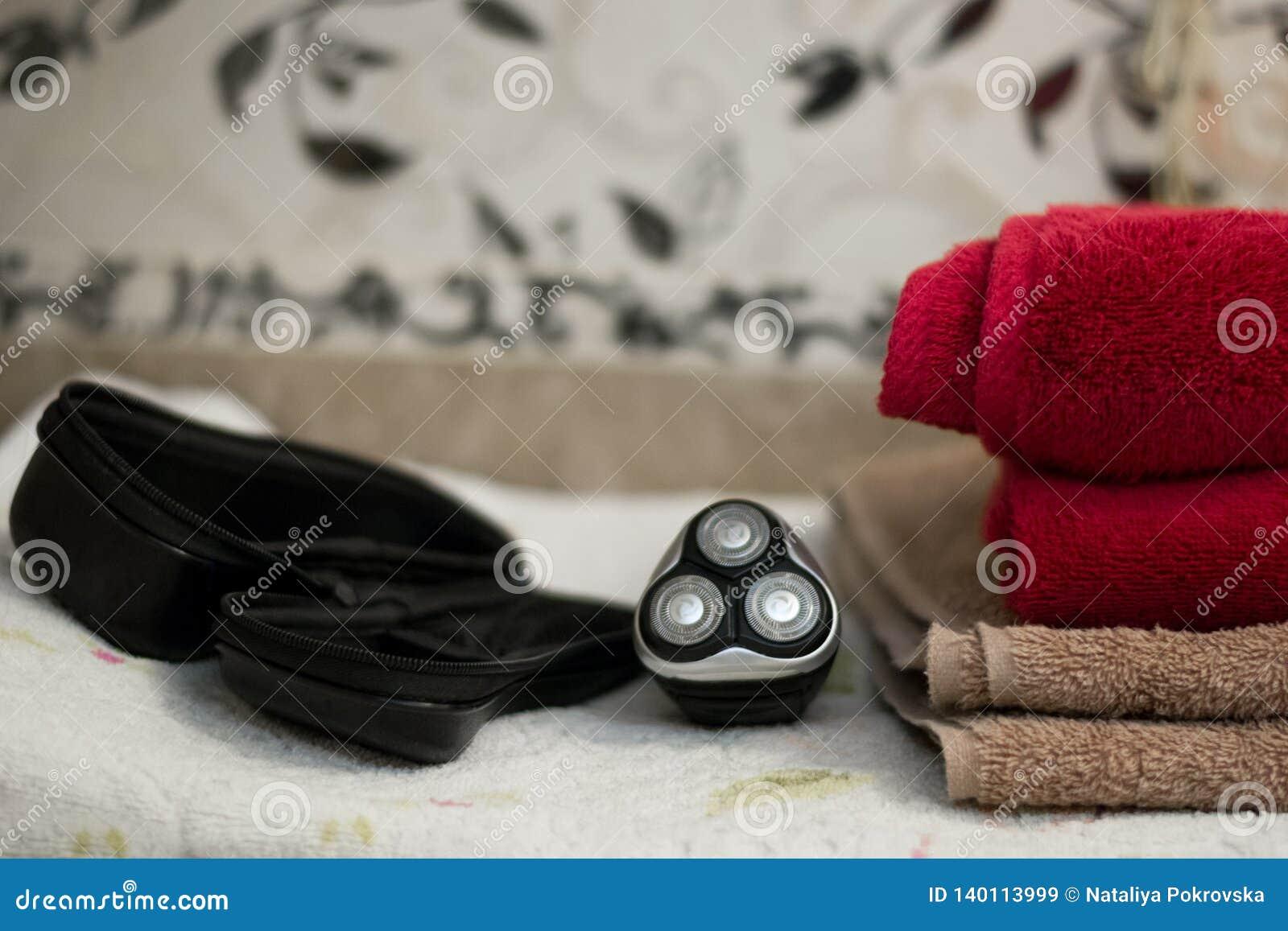 Elektrisch blauw roterend scheerapparaat met drie bladen dichtbij zwart geval en badhanddoeken