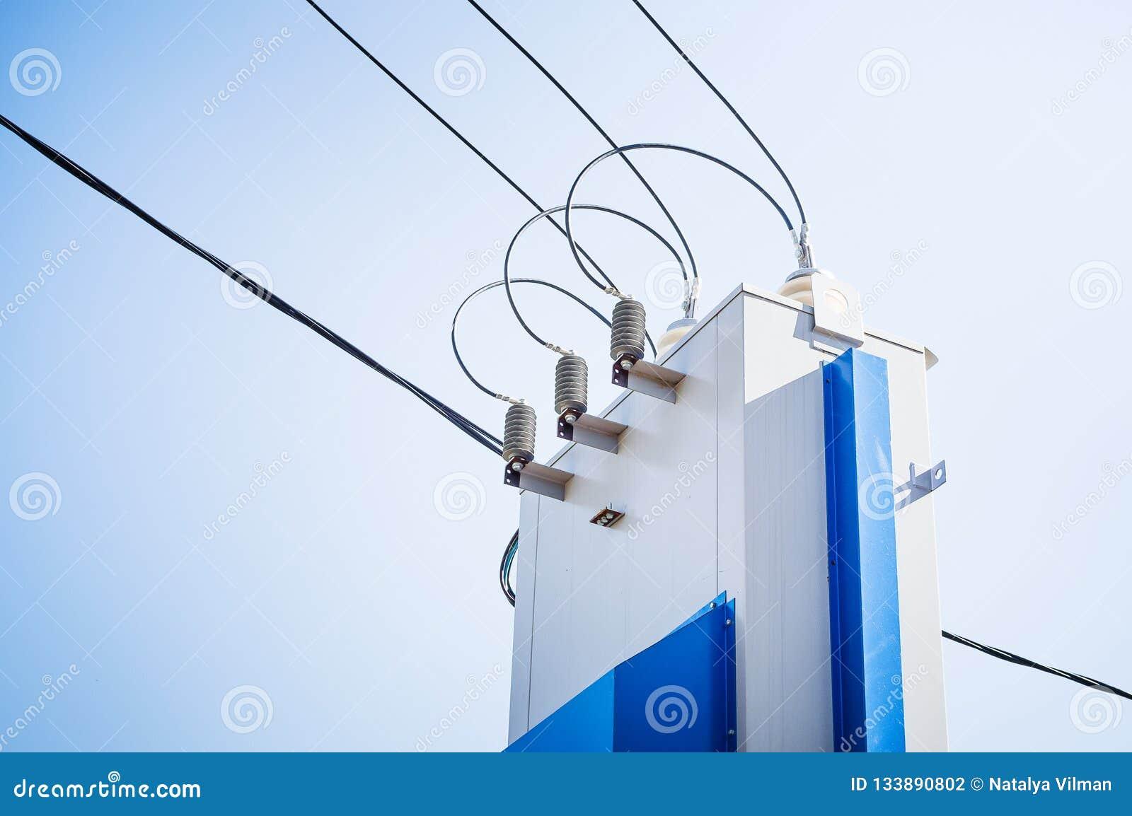 Elektrische raad met draden met hoog voltage tegen de blauwe hemel