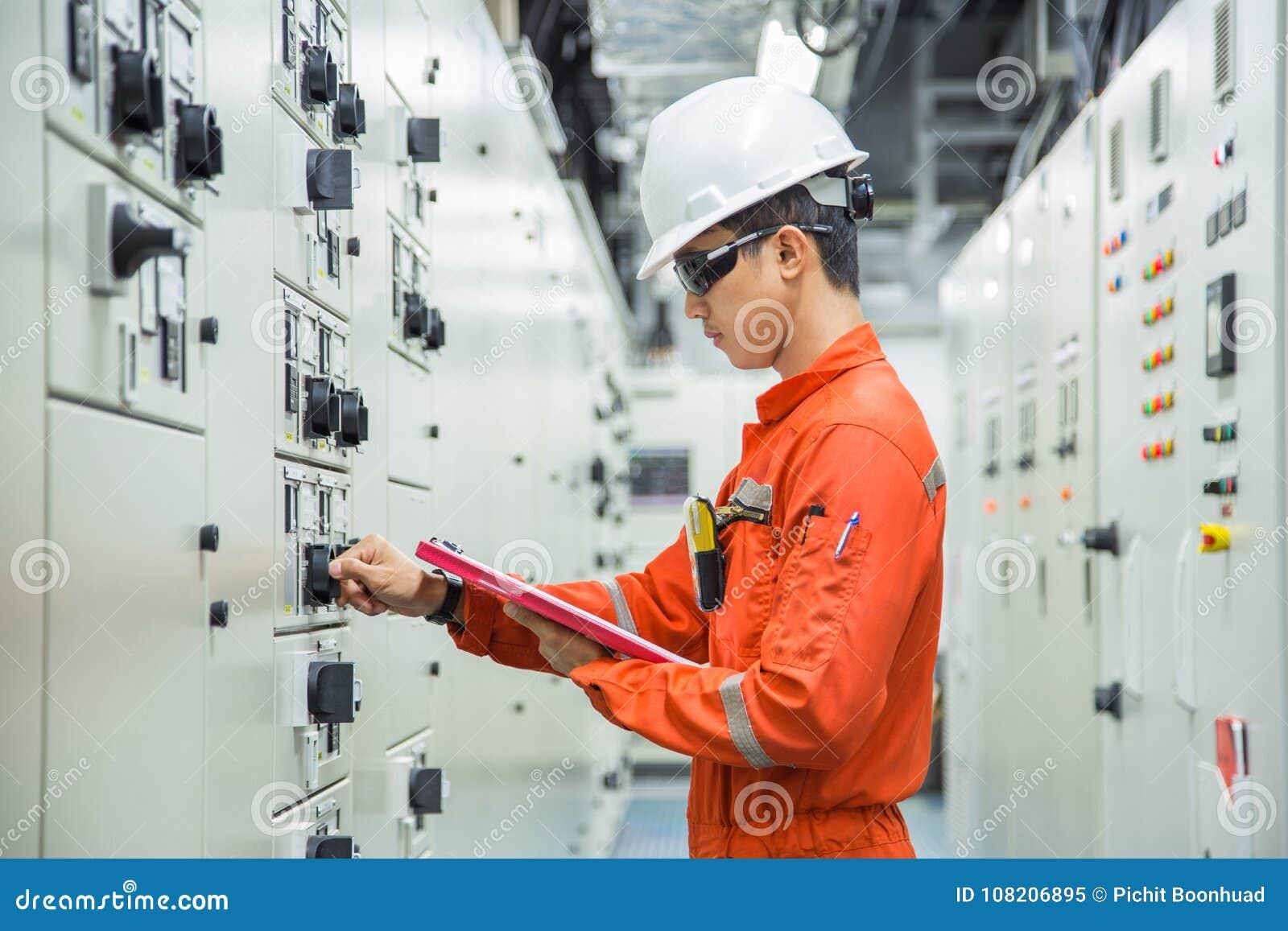 Elektrischer und Instrumenttechniker, der elektrische Kontrollorgane des Bewegungsanfangssystems im Schalteinheitsraum überprüft