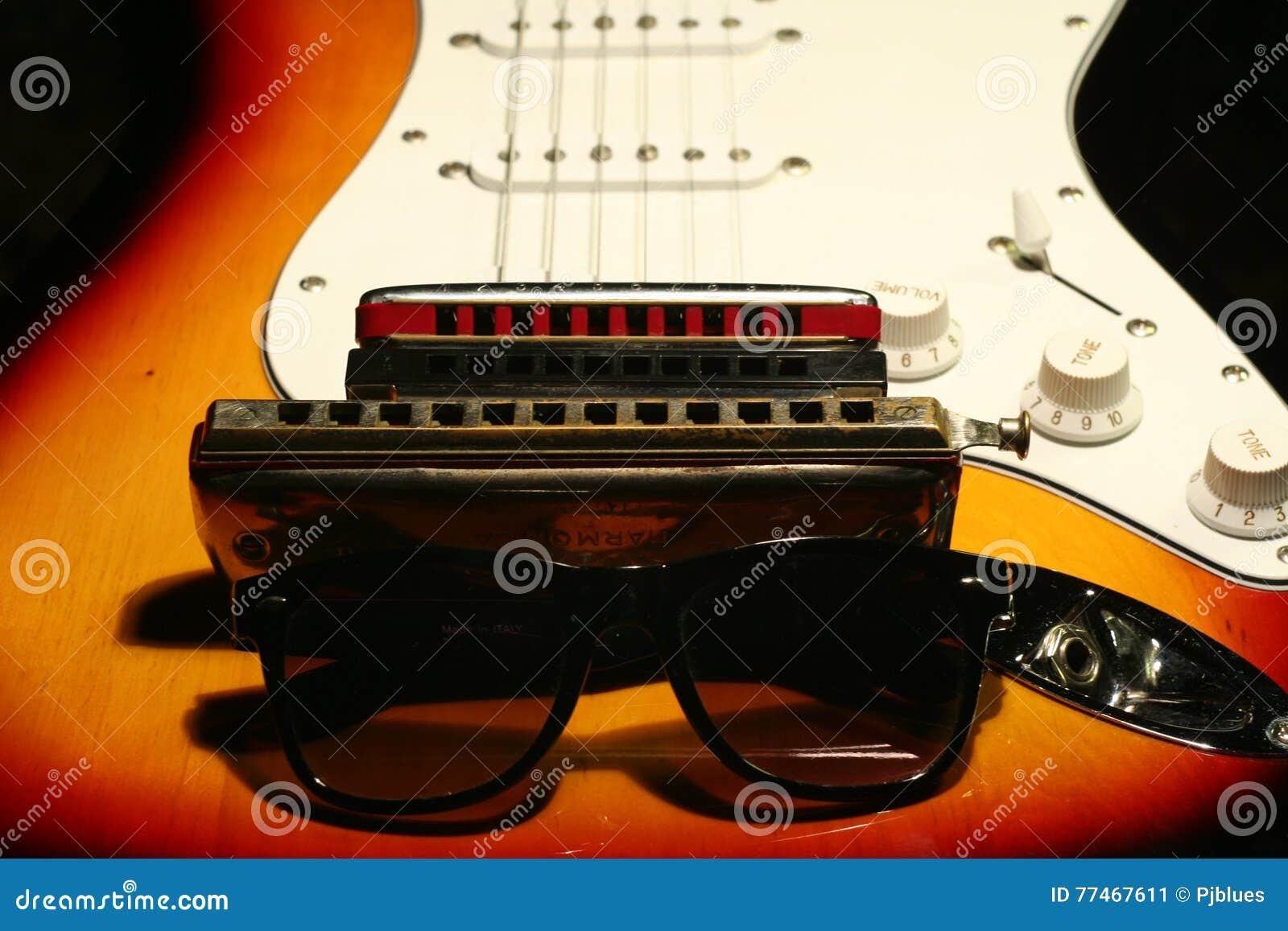Elektrisk gitarr för tappning, munspel, solglasögon på svart bakgrund