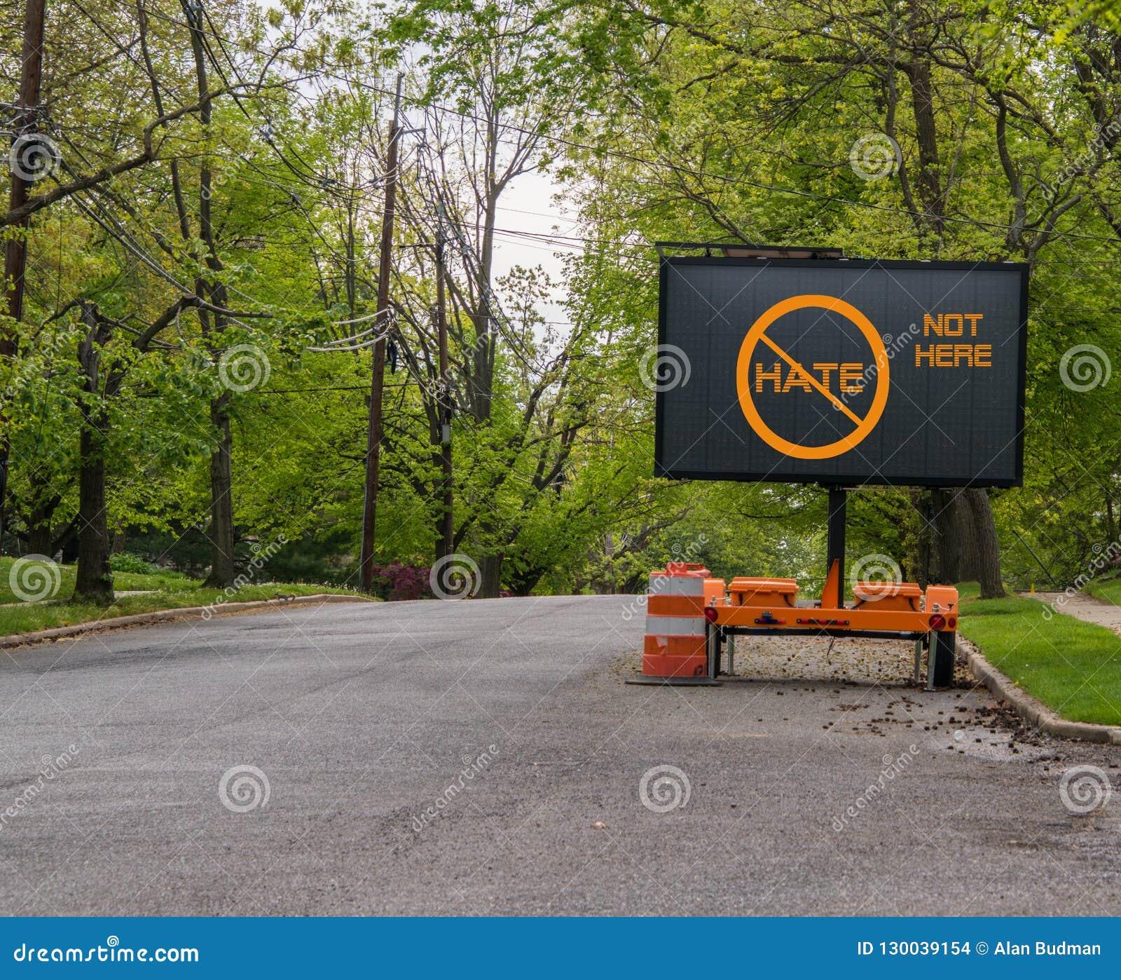 Elektriskt trafikgatatecken på den tysta grannskapgatan, som säger inget hat, inte här