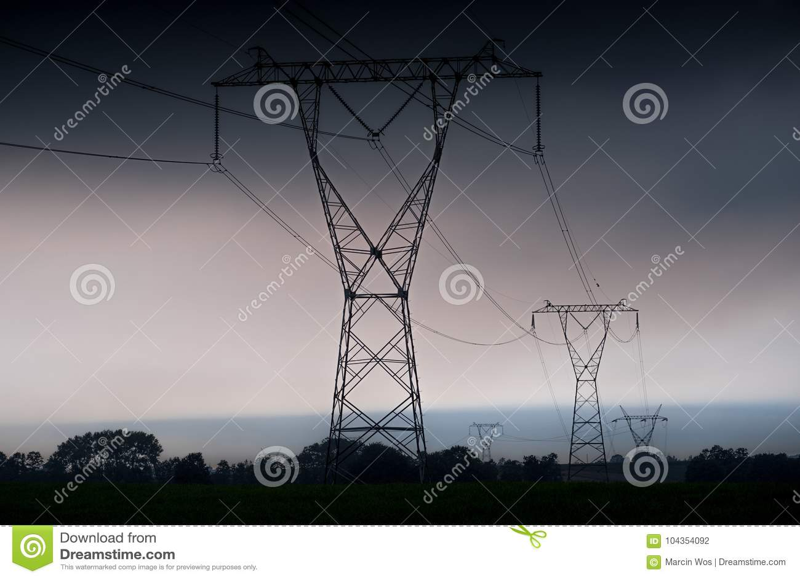 ElektrizitätsübertragungsStromleitungen am Sonnenuntergang Hochspannungsturm
