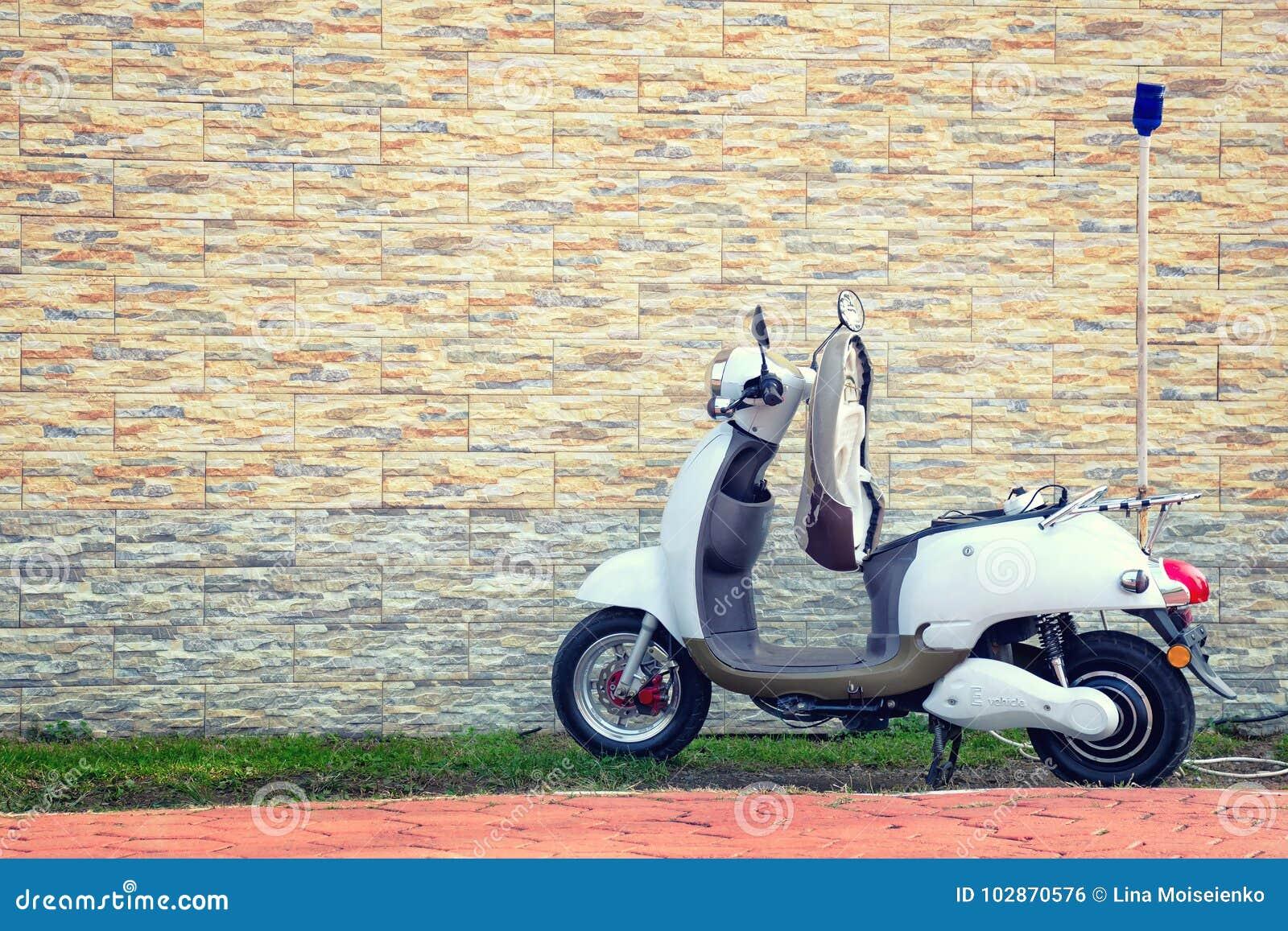 Elektromotorroller parkte nahe einer schönen Wand für die Aufladung