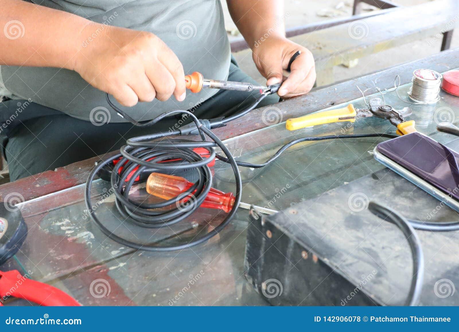 Elektronika technika mężczyźni naprawiają elektrycznych urządzenia Związek łamani druty z lutowniczymi maszynami