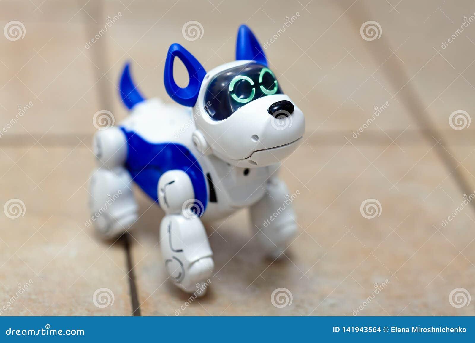 Elektronisch interactief stuk speelgoed hondpuppy op een beige ceramische vloerachtergrond van selectieve nadruk