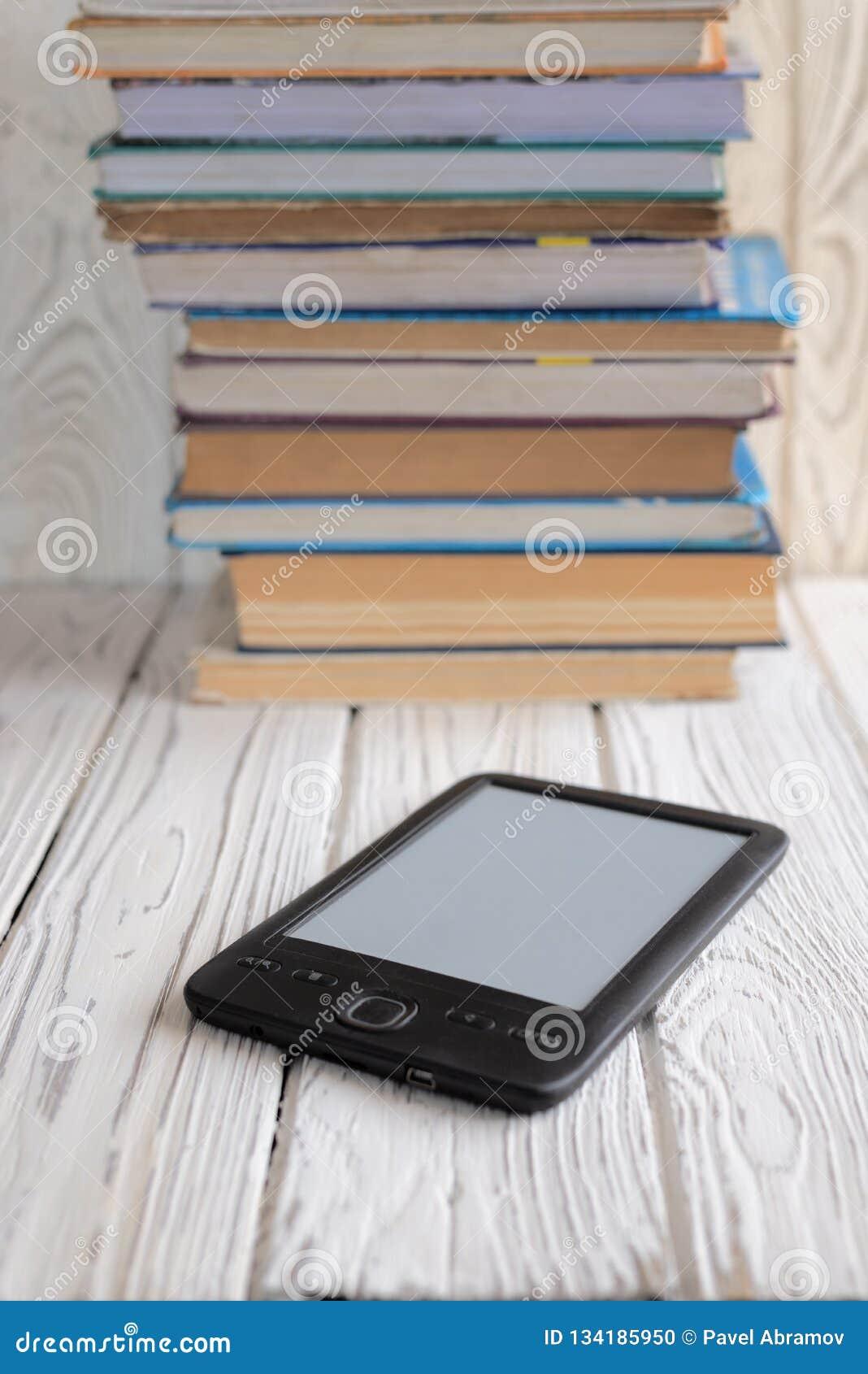 Elektronisches Buch gezeigt gegen einige regelmäßige Lehrbücher