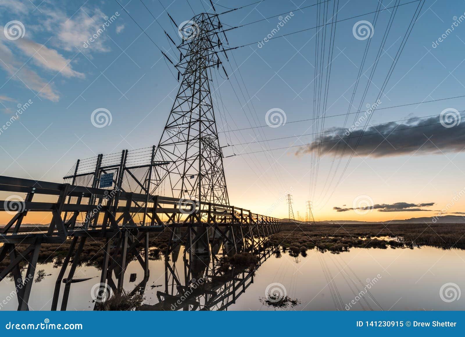 Elektrotorens met belangrijke lijnen bij zonsondergang, met bezinningen in water