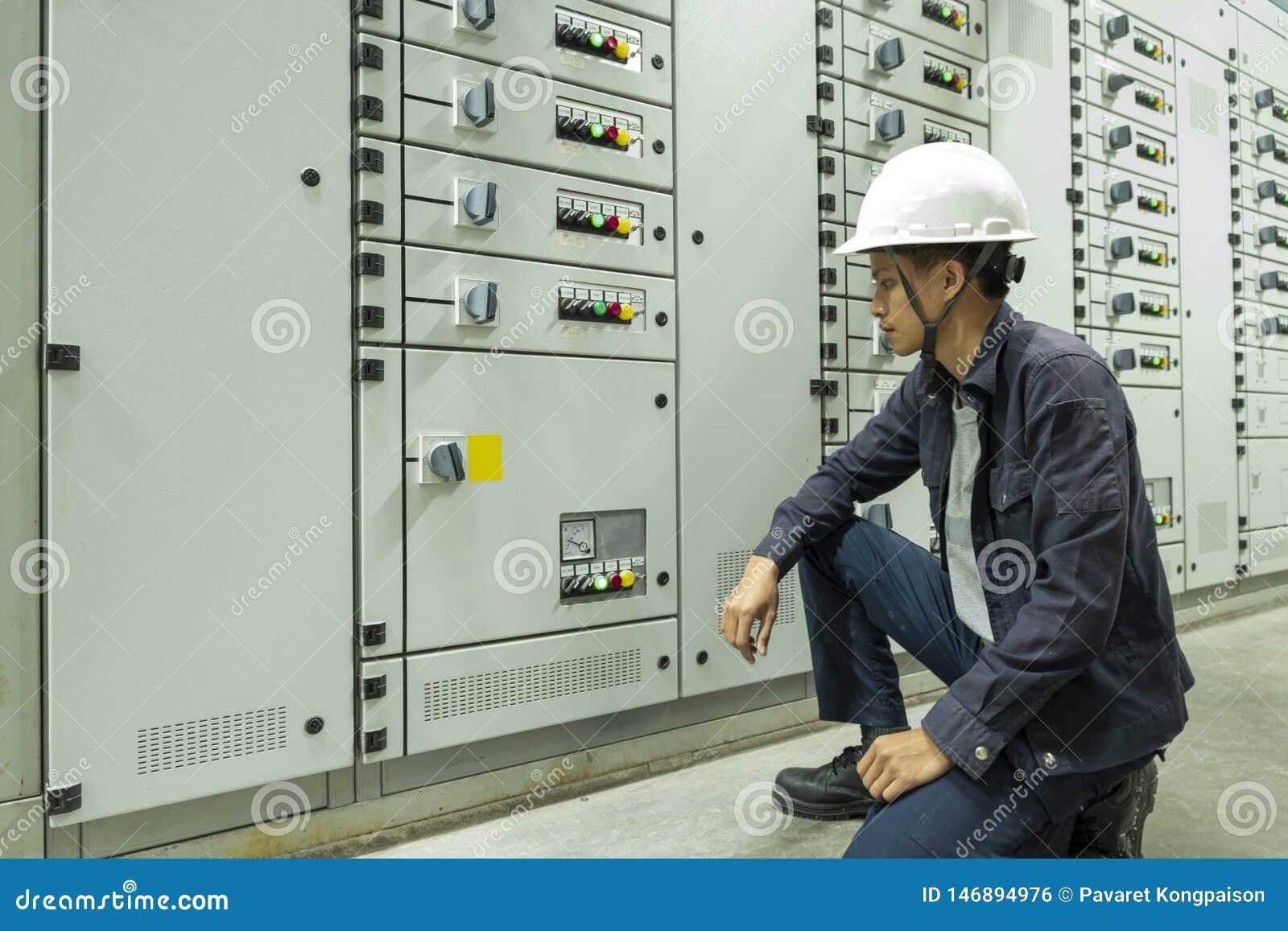 Elektrycy sprawdzaj? elektrycznych pulpit operatora w przemys?owych ro?linach