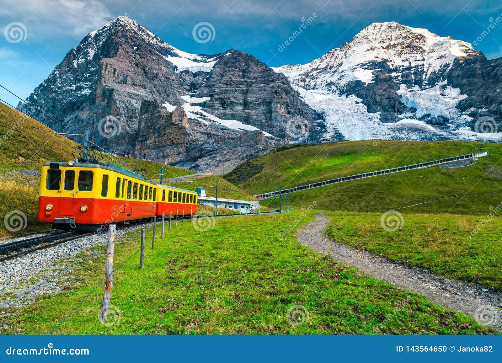 Elektrycznego turysty taborowa i śnieżna Eiger góra, Bernese Oberland, Szwajcaria