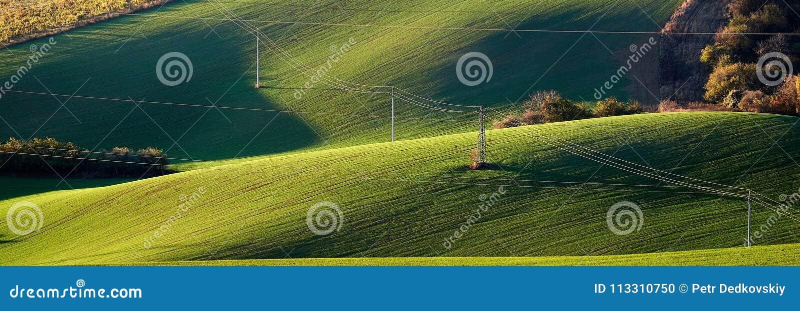 Elektryczność linie energetyczne na zielonych wzgórzach iluminujących wieczór słońcem i pilon Południe Morawscy cesky krumlov rep