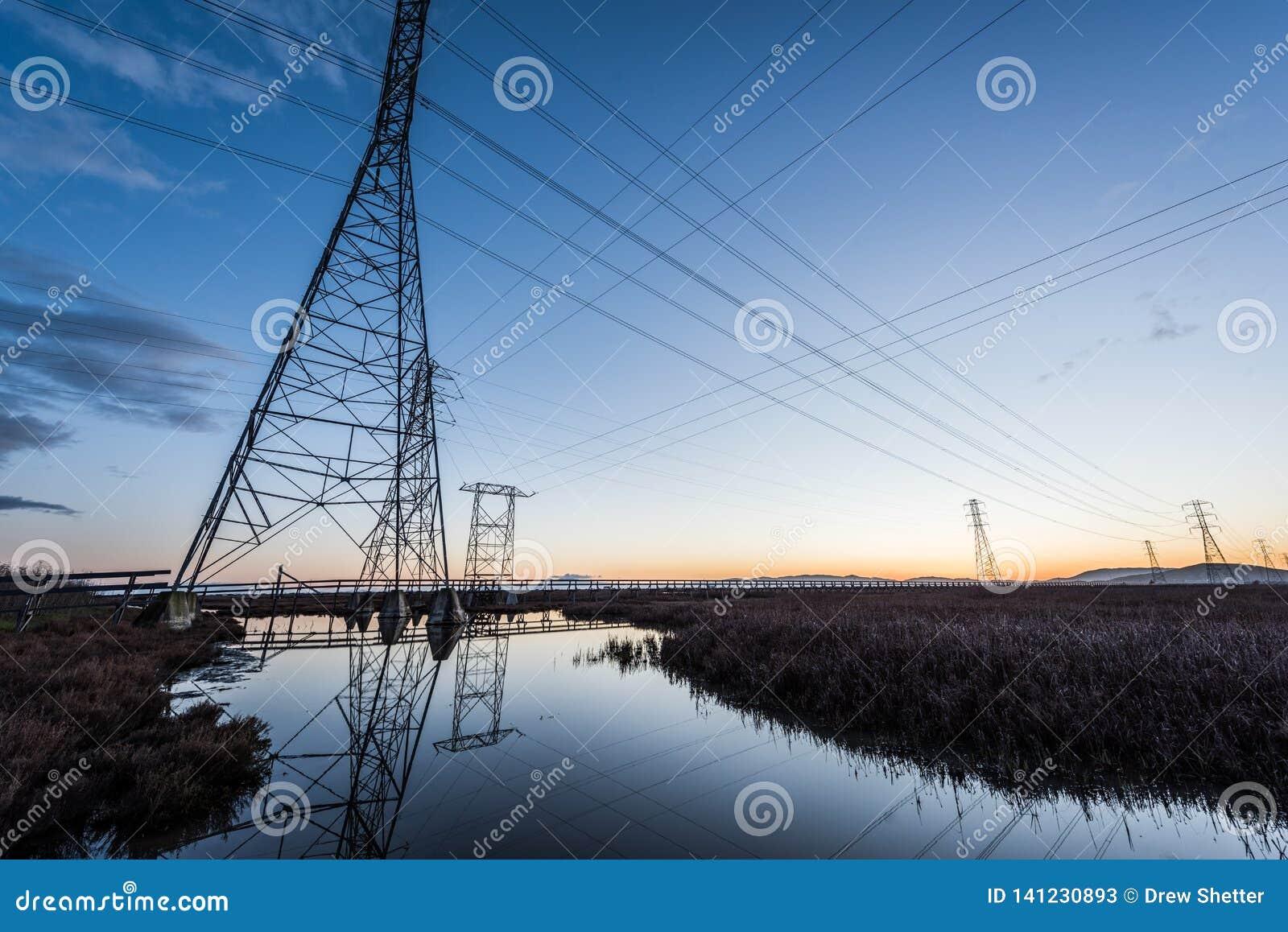 Elektryczny góruje z prowadzić linie przy zmierzchem, z odbiciami w wodzie