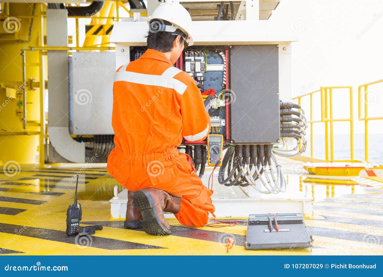 Elektryczny i instrument pracownik sprawdza dla preventiv i sprawdzać woltaż i prąd elektryczny system przy ropa i gaz platformą