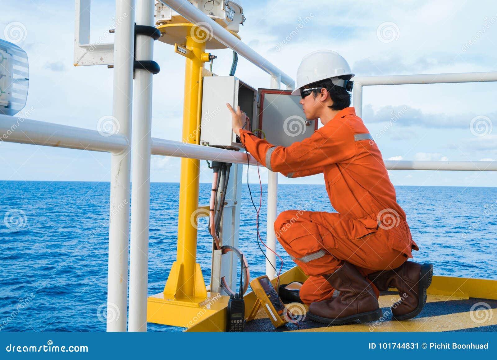 Elektryczny i instrument technik jest wizytacyjny na oświetleniu nawigaci pomocy system przy ropa i gaz wellhead pilota platformą