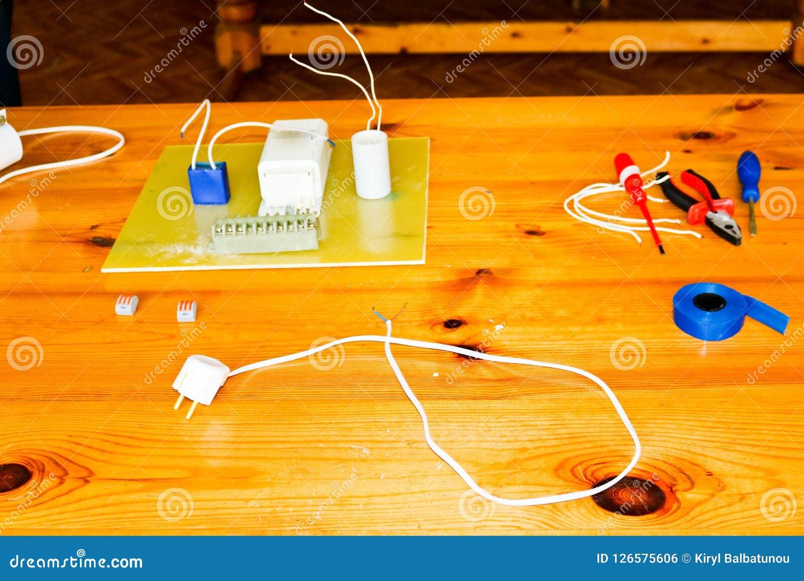 Elektryczny obwód z drutami i dodatkowymi częściami, instalacyjny wyposażenie, cążki, błękitna elektryczna taśma, śrubokręty na s