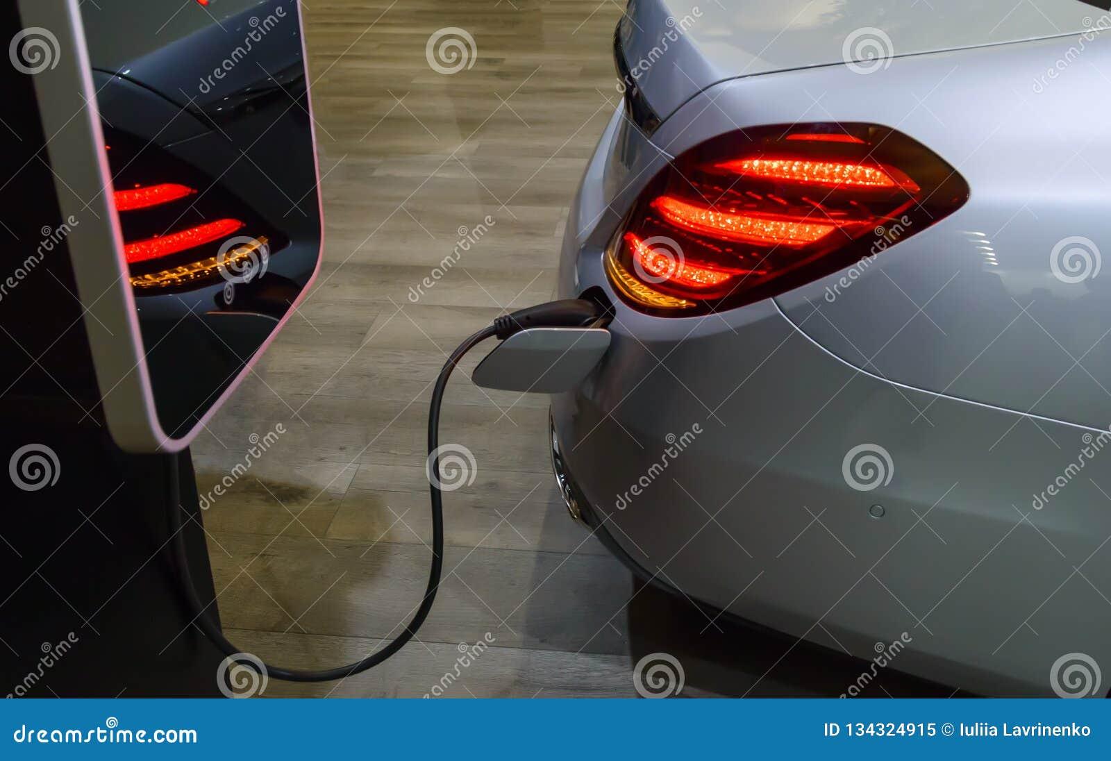 Elektryczny samochód z czopuję w władza kablu przy ładuje stacją