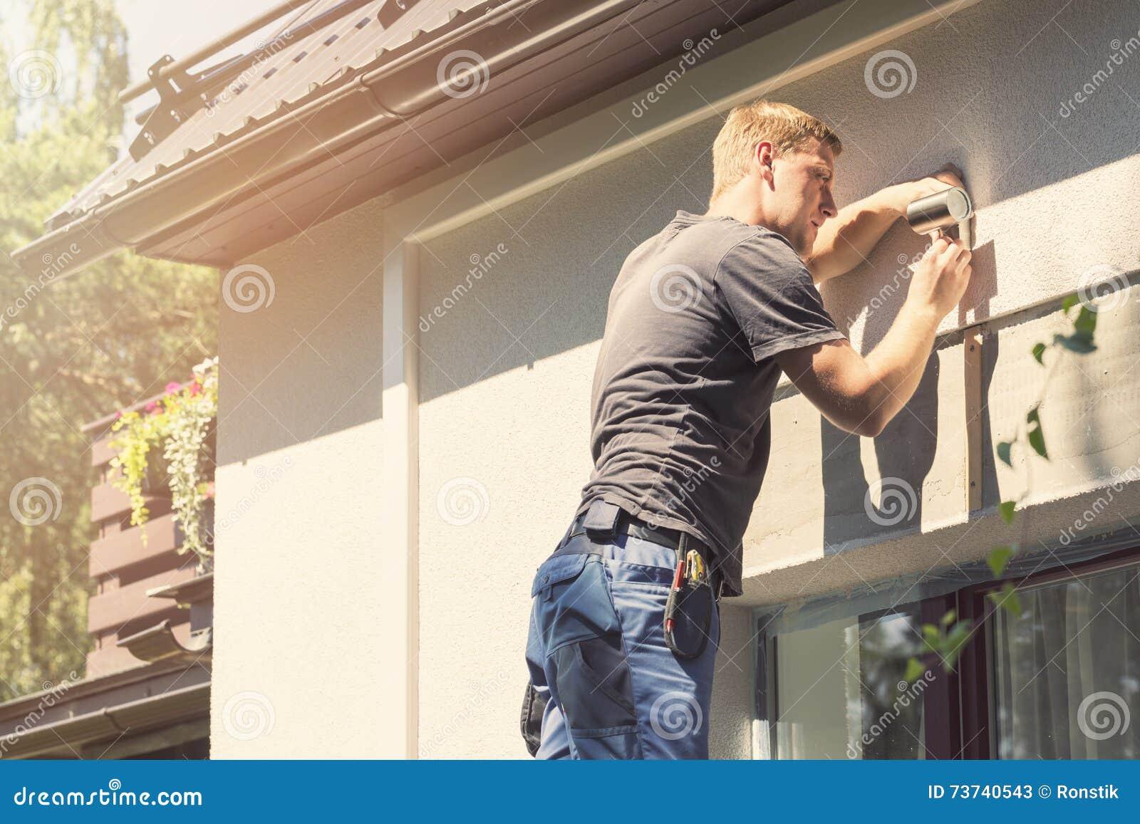Elektryk instaluje lampę na domowej fasadzie