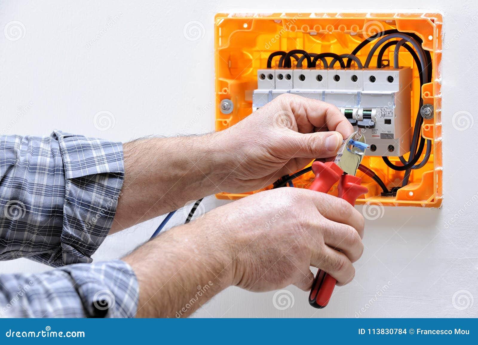 Elektryka technik przy pracą na mieszkaniowym elektrycznym panelu