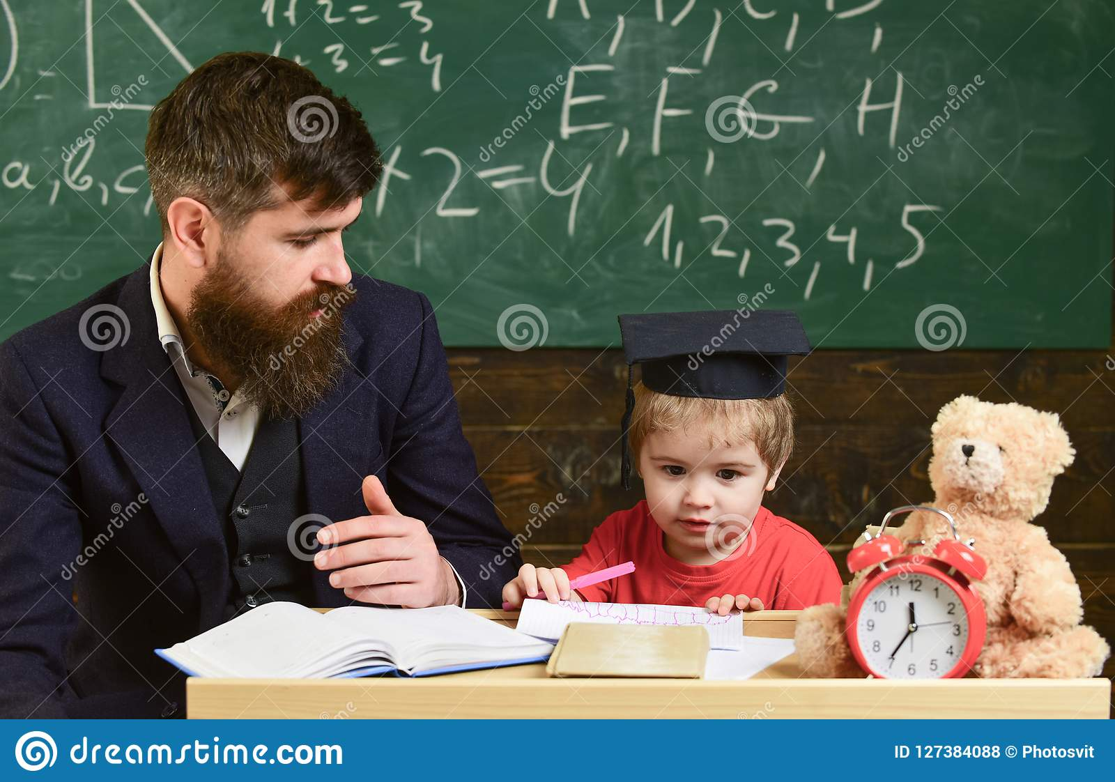 Elementary education. Kid studying with teacher. Father teaches son, discuss, explain. Education concept. Teacher in
