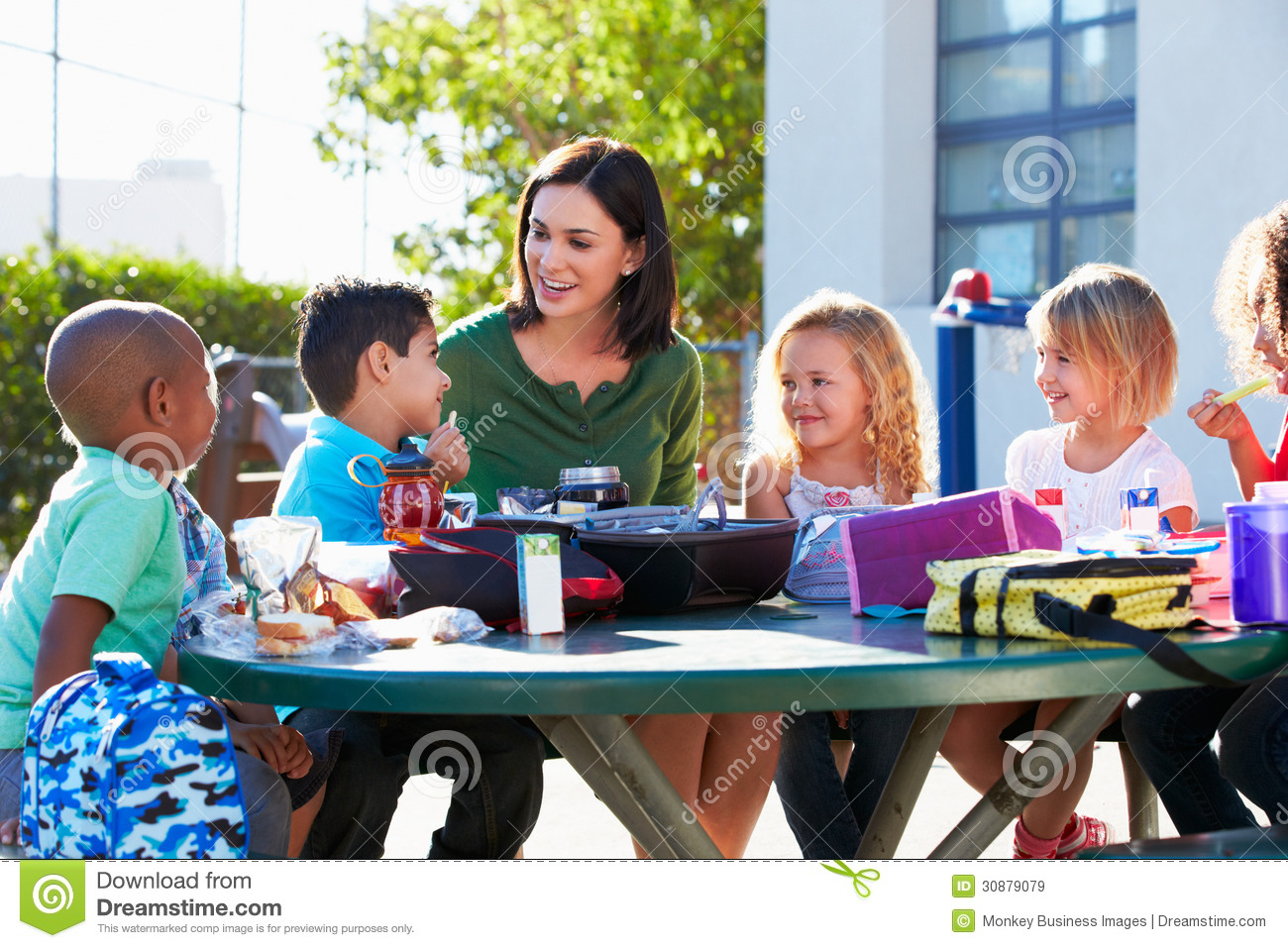 Elementary Pupils And Teacher Eating Lunch