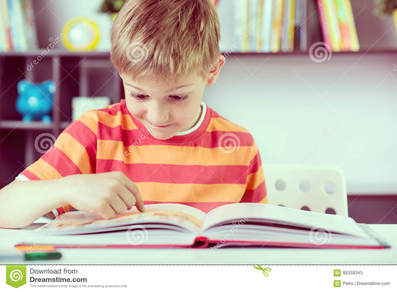 Elementary school boy at desk reading boock