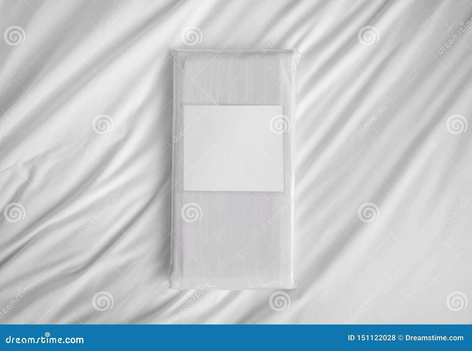Elementi a strisce della biancheria da letto del tessuto nella borsa del PVC con l etichetta vuota contro lo strato bianco