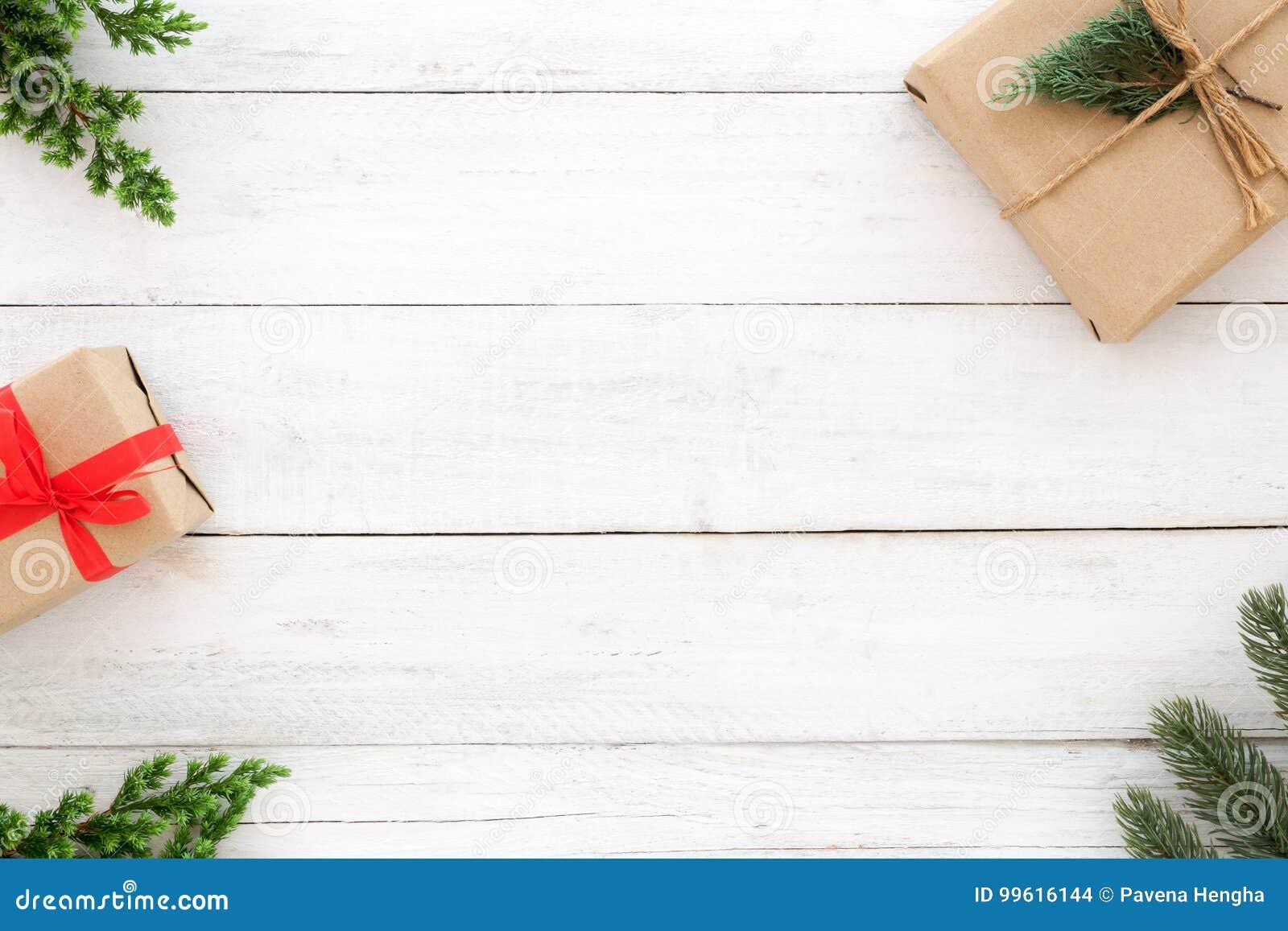 Elementos rústicos da decoração das caixas de presente do presente de Natal e das folhas do abeto no fundo de madeira branco