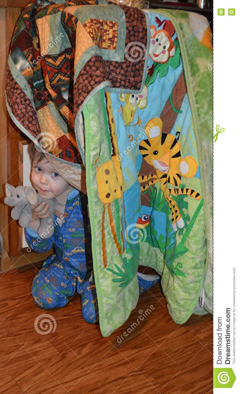 Elephant-loving toddler and his elephant peeking out of a blanket fort