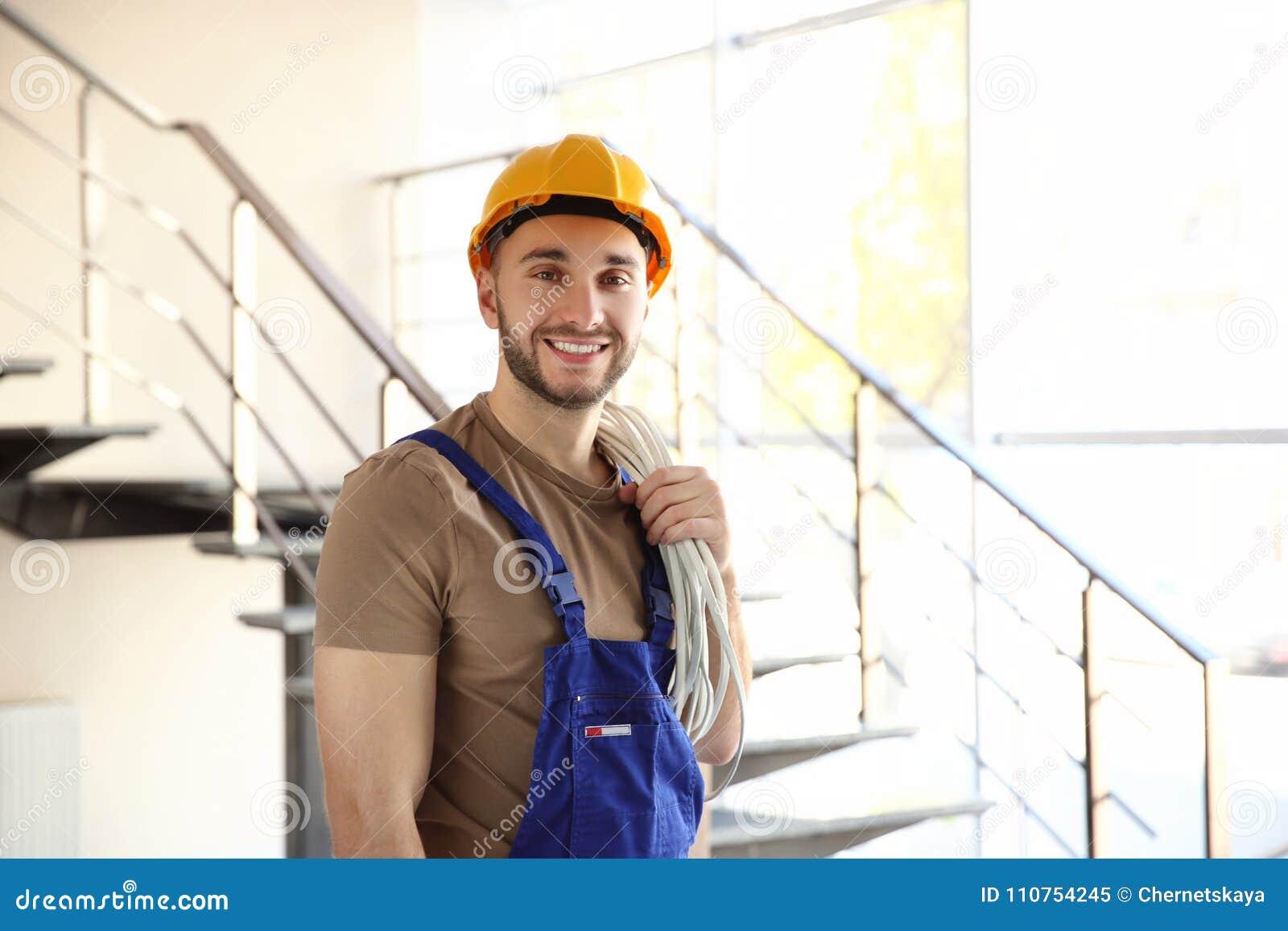 Eletricista de sorriso novo que guarda o grupo dos fios e da posição