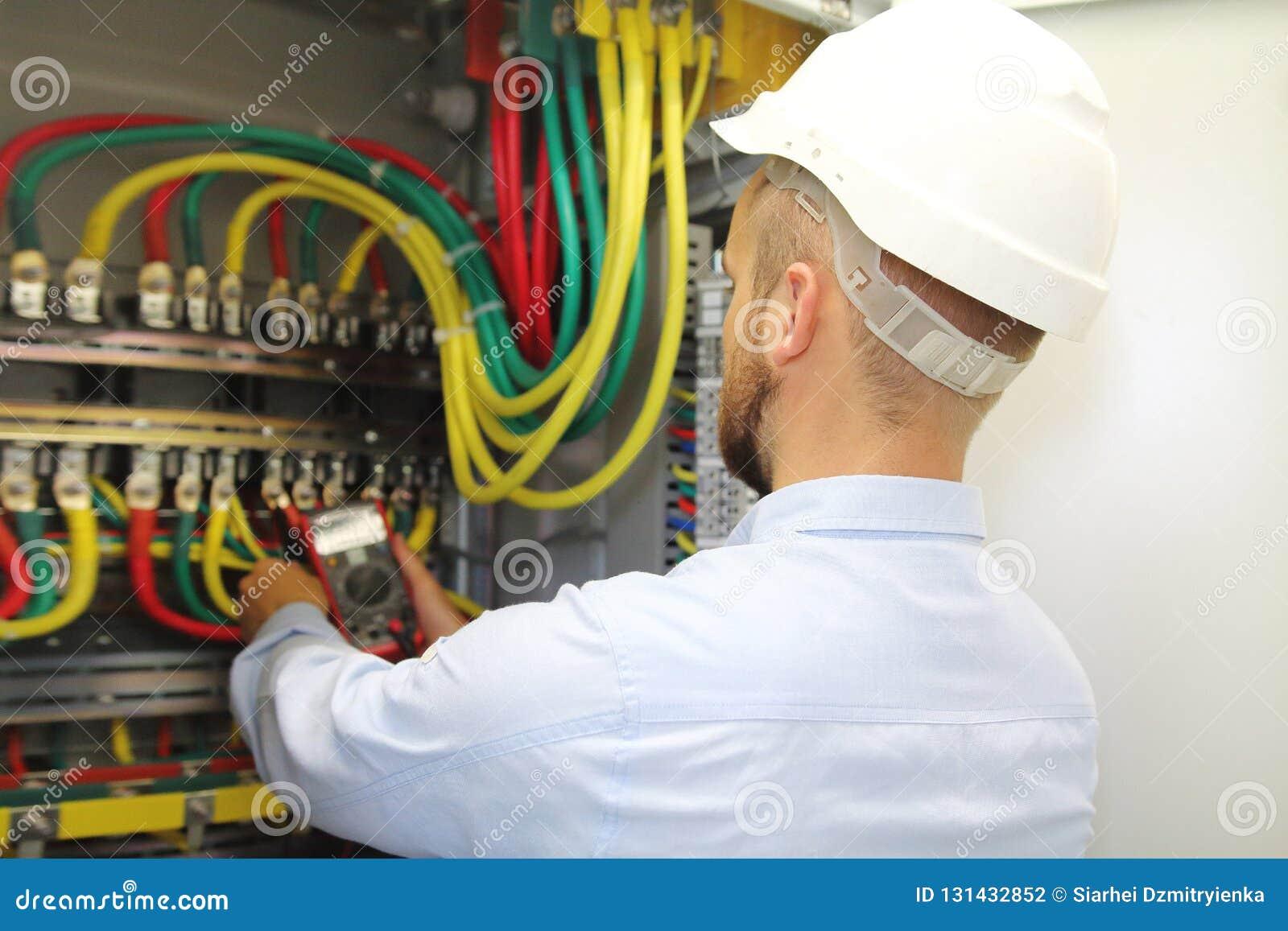 Eletricista em medidas da tensão do trabalho no fuseboard industrial da distribuição