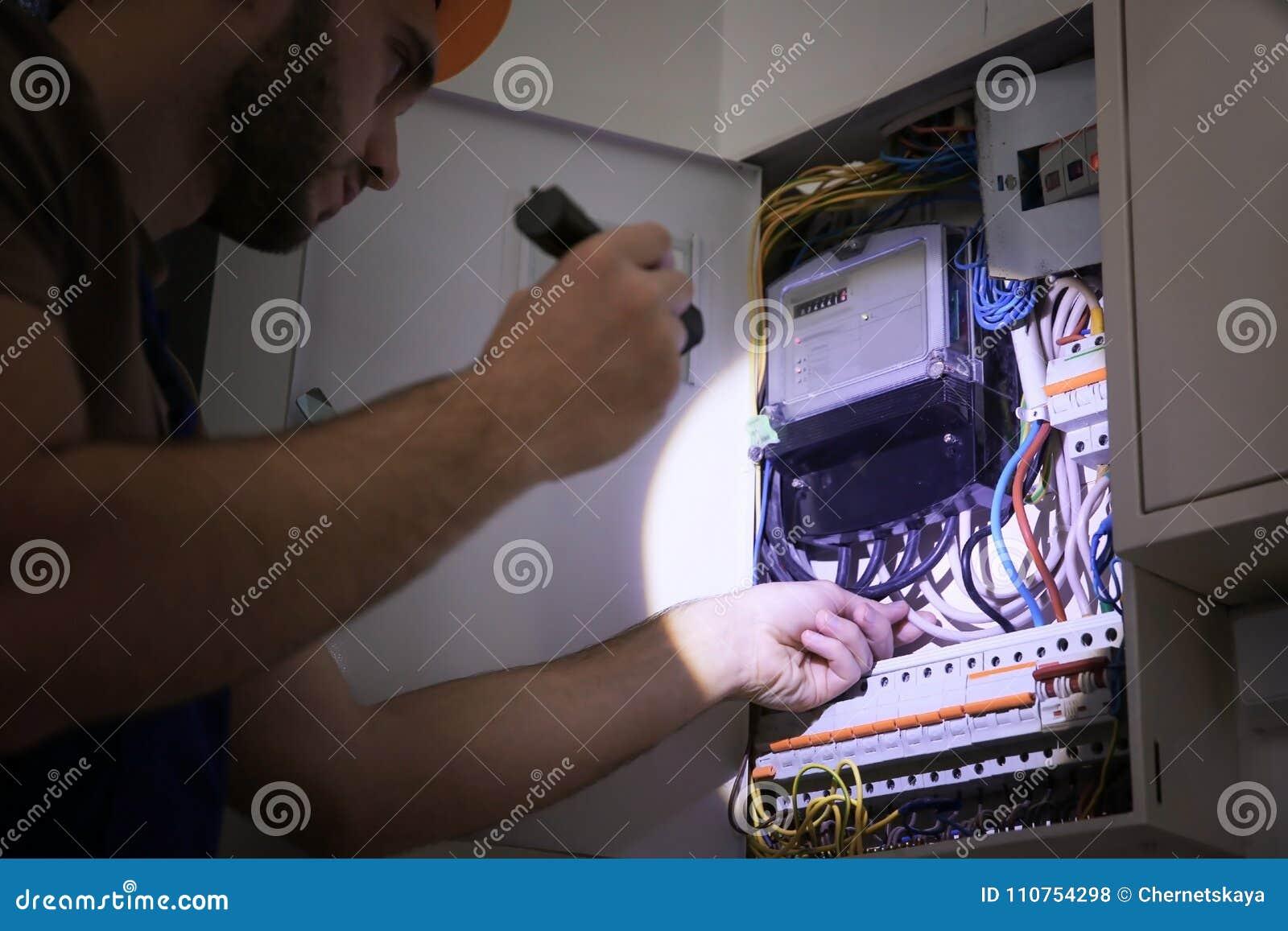Eletricista novo com a lanterna elétrica perto da caixa de interruptor