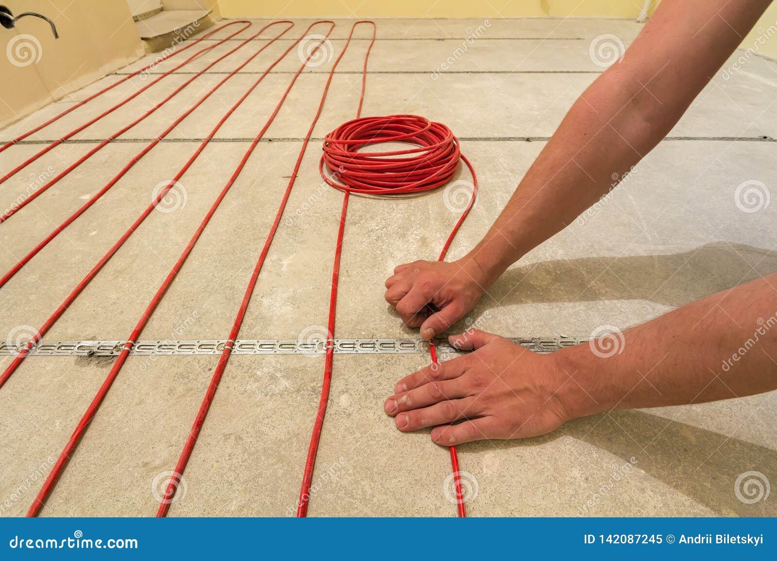 Eletricista que instala o fio vermelho de aquecimento do cabo elétrico no assoalho do cimento na sala inacabado Renovação e const