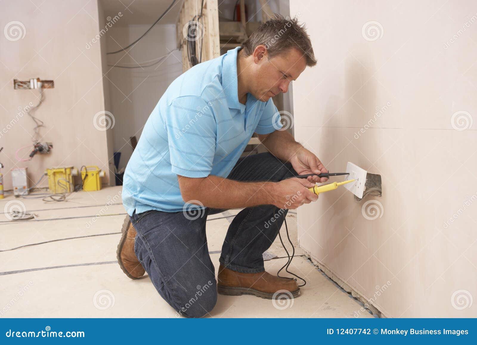 Eletricista que instala o soquete de parede