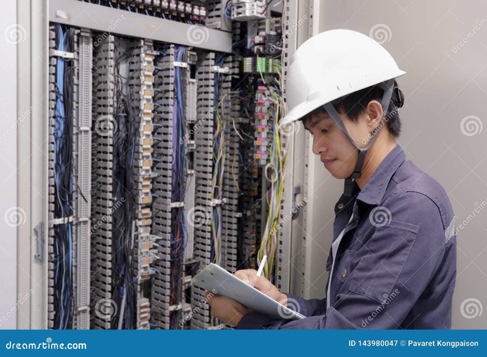 Eletricistas que sorriem, inspecionando caixas elétricas na fábrica industrial