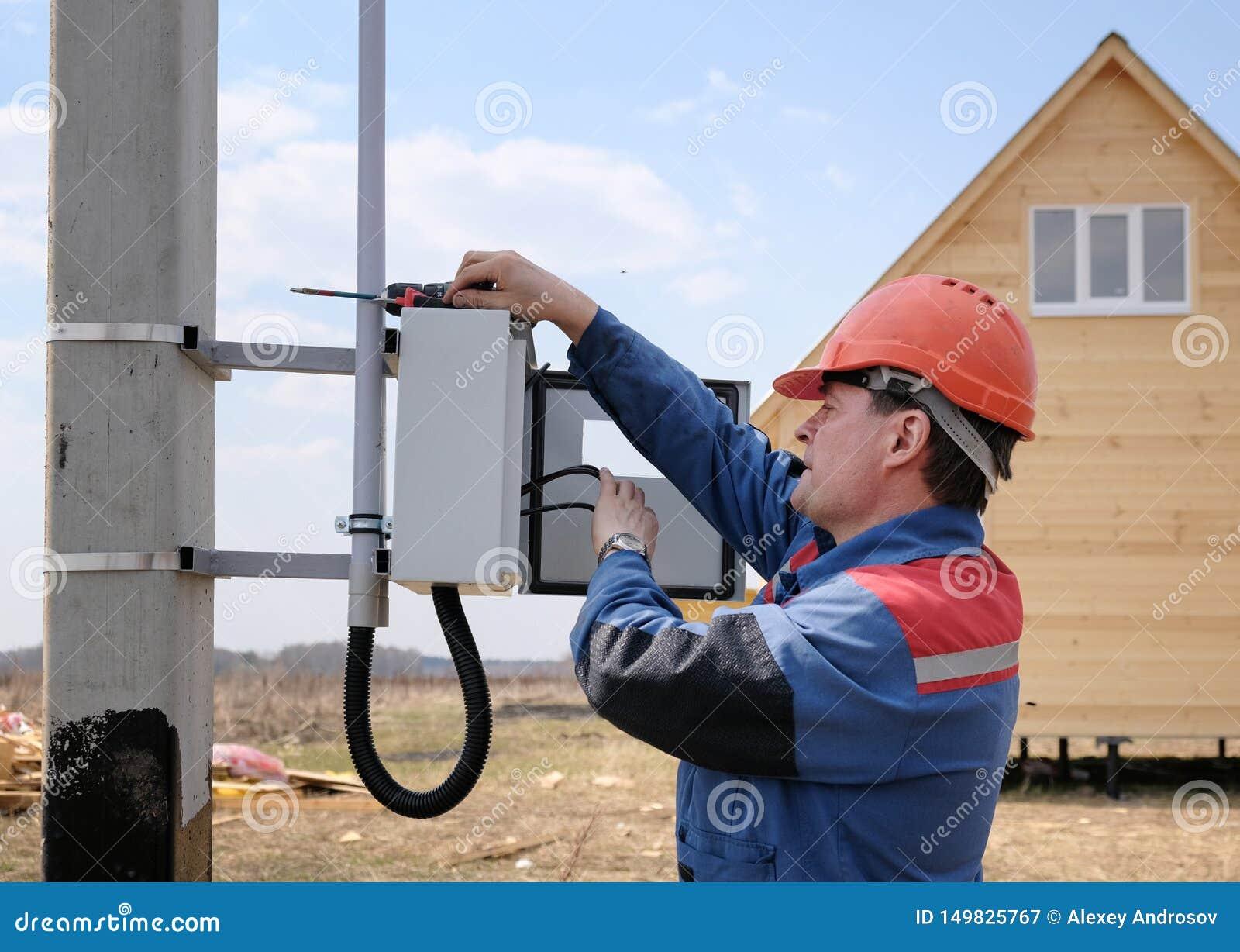 Elettricista impegnato nell installazione del metro di elettricit? sul supporto delle linee elettriche il processo dell elettrici