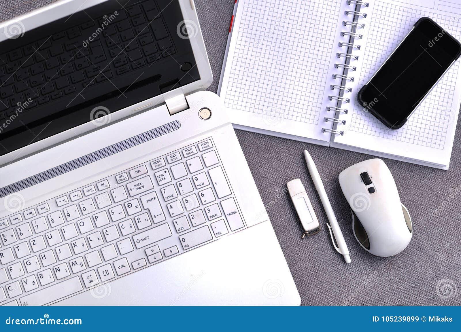 Elevação acima da vista do local de trabalho do escritório com o teclado e o rato ascendentes próximos de computador do telefone
