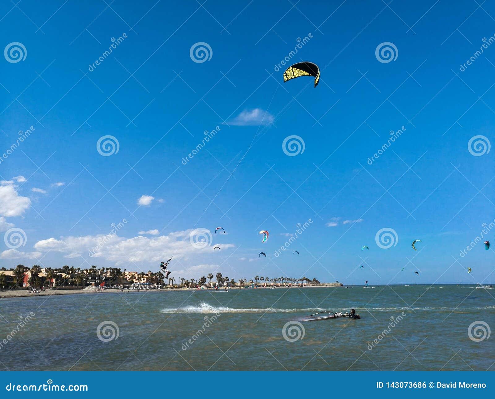 Elevação do voo do desportista do embarque do papagaio com papagaio e kiteboard nas botas no céu azul, esportes ativos e estilo d